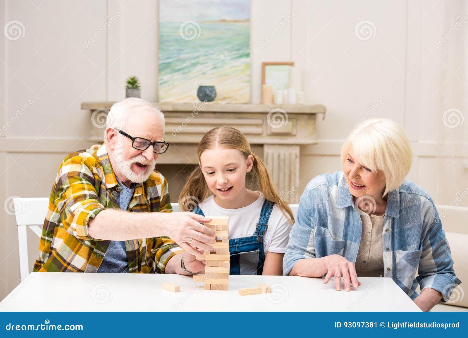Kleines Mädchen mit dem Großvater und Großmutter, die zu Hause jenga Spiel spielen