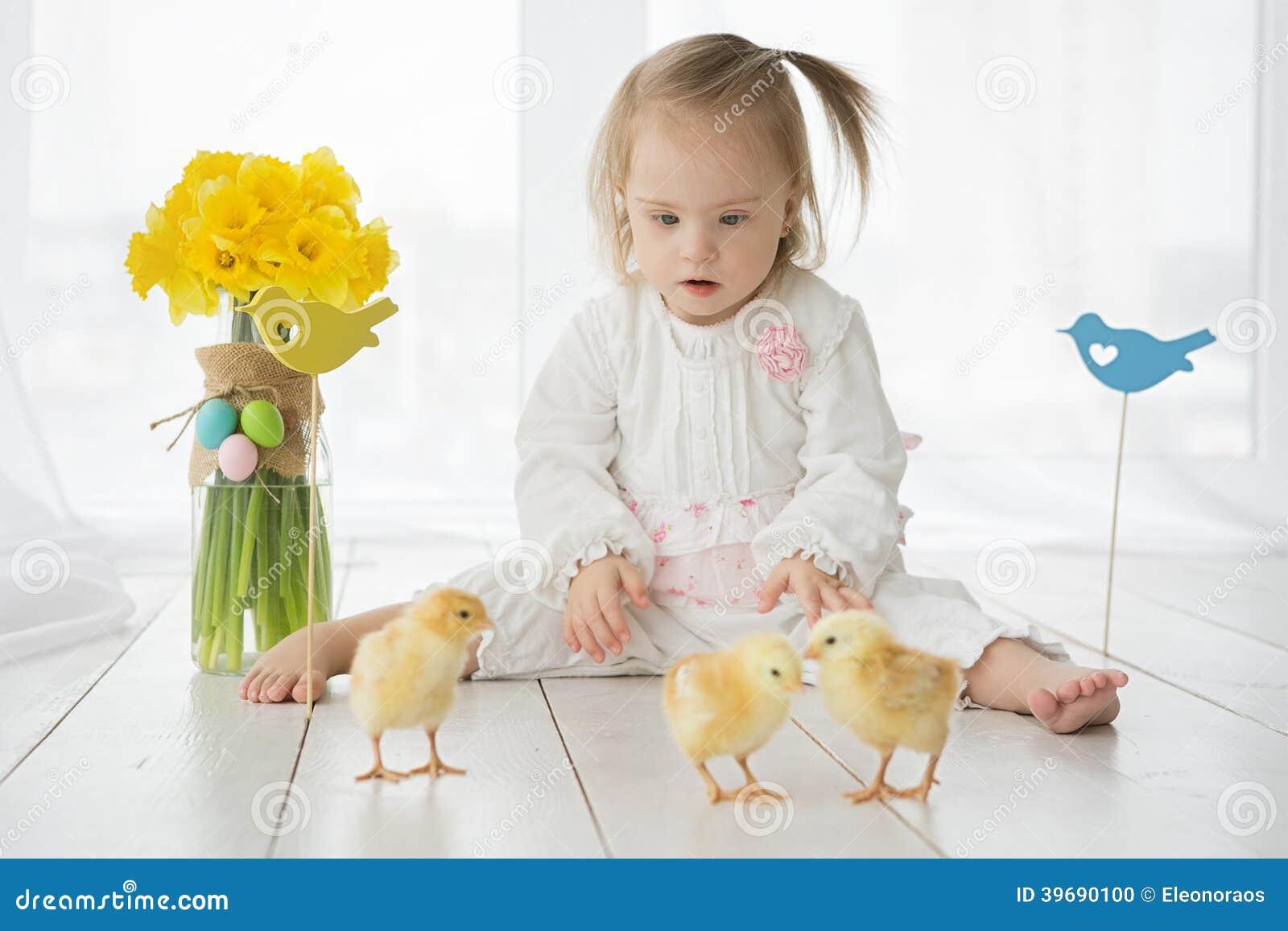 Kleines Mädchen mit Down-Syndrom, das mit gelben Hühnern spielt