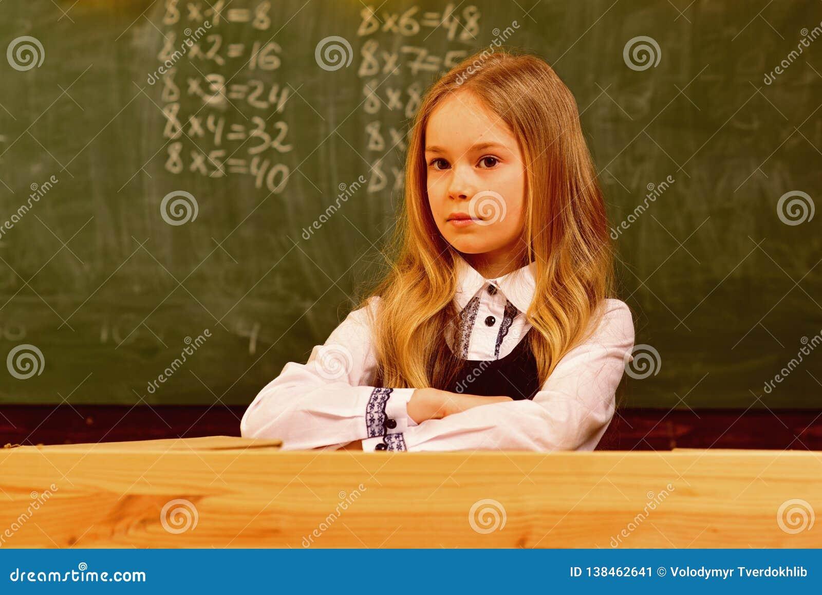 Kleines Mädchen kleines Mädchen mit ernstem Gesicht in der Schule kleine Lektion des Mädchens in der Schule kleines Mädchen ist b