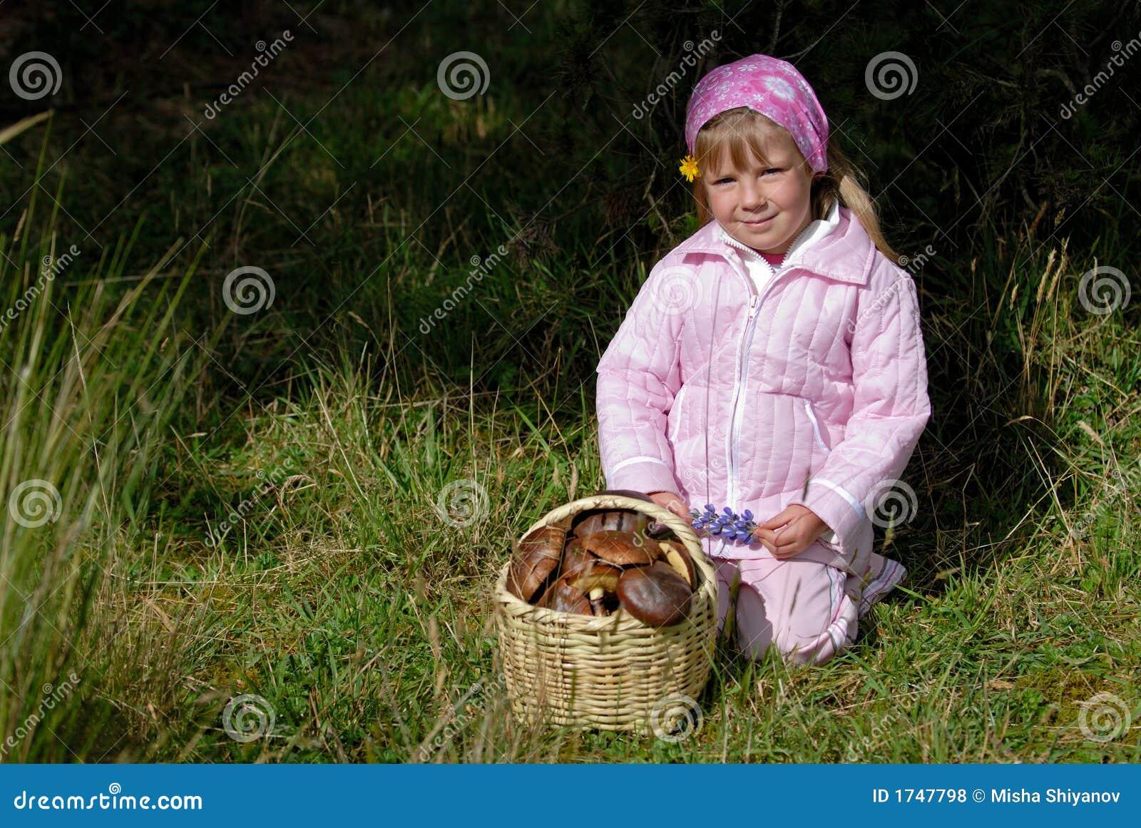 Kleines Mädchen mit Korb der Pilze