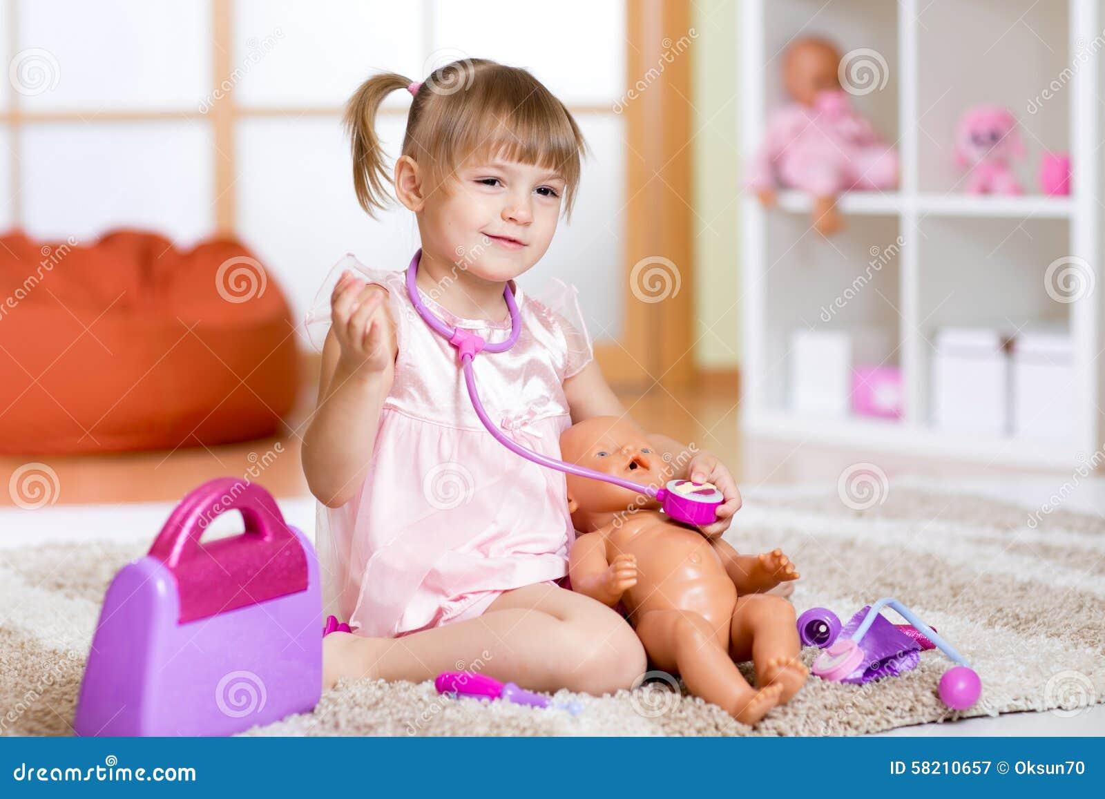 Kleines Mädchen spielt Doktor, der einen Puppenpatienten überprüft