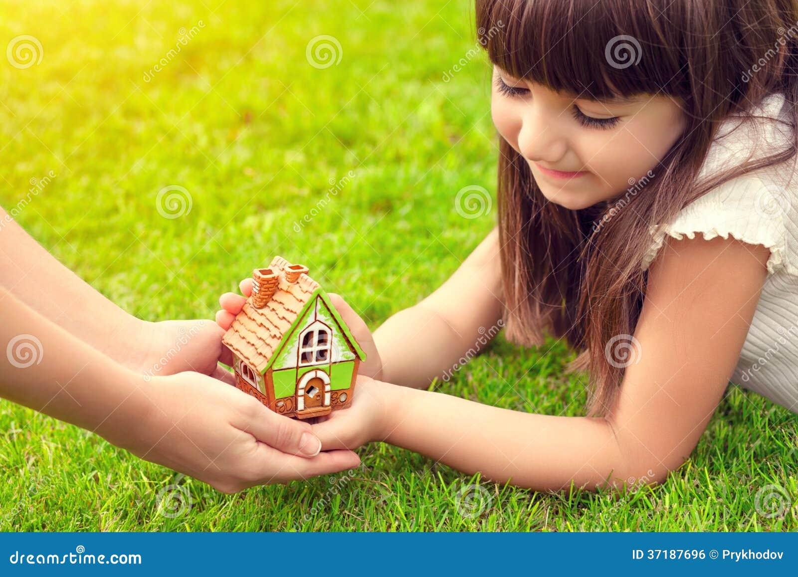 Kleines Mädchen und eine Frau übergibt das Halten des kleinen Hauses auf einem backgroun