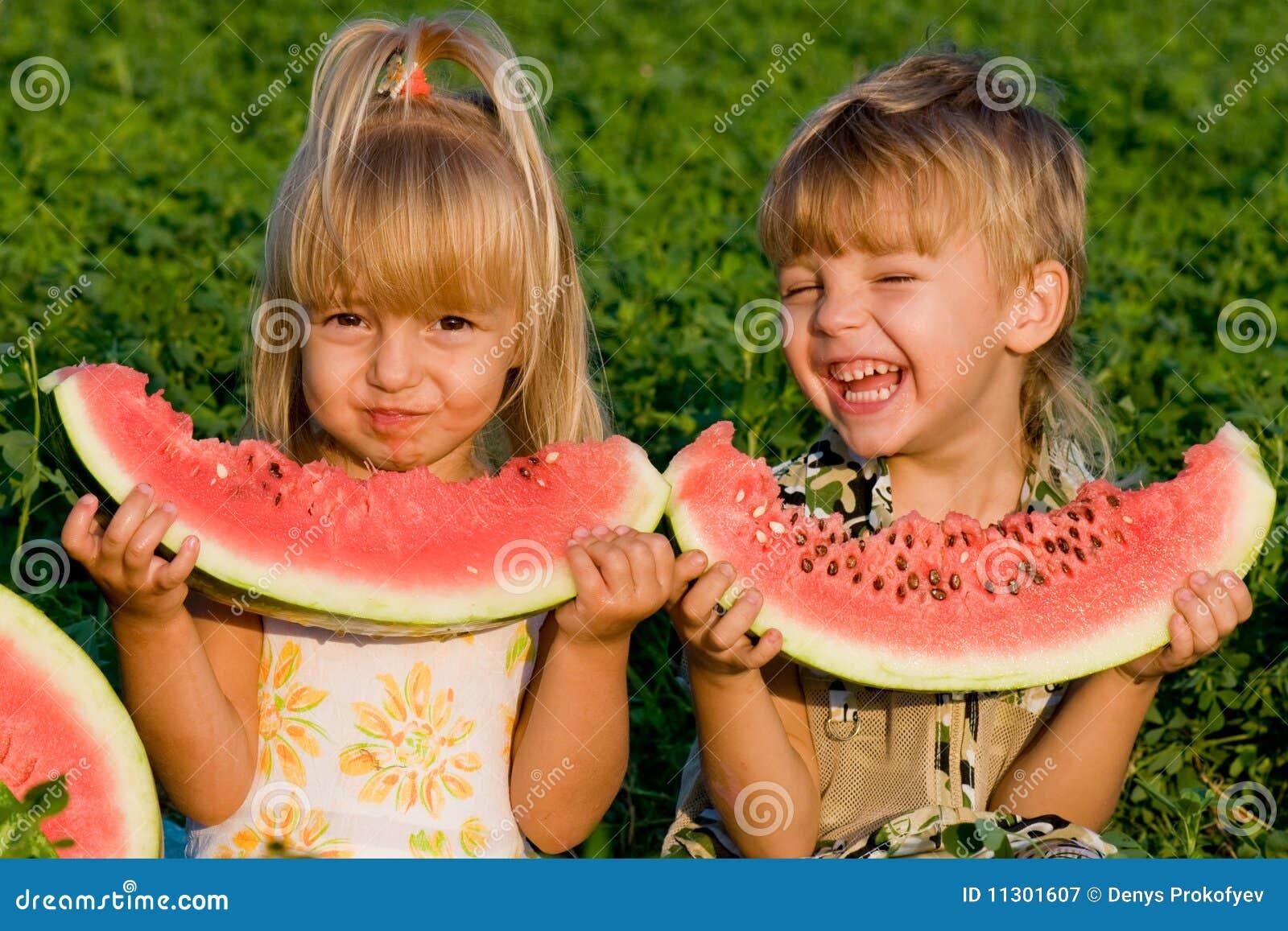 Kleines Mädchen und Junge mit Wassermelone