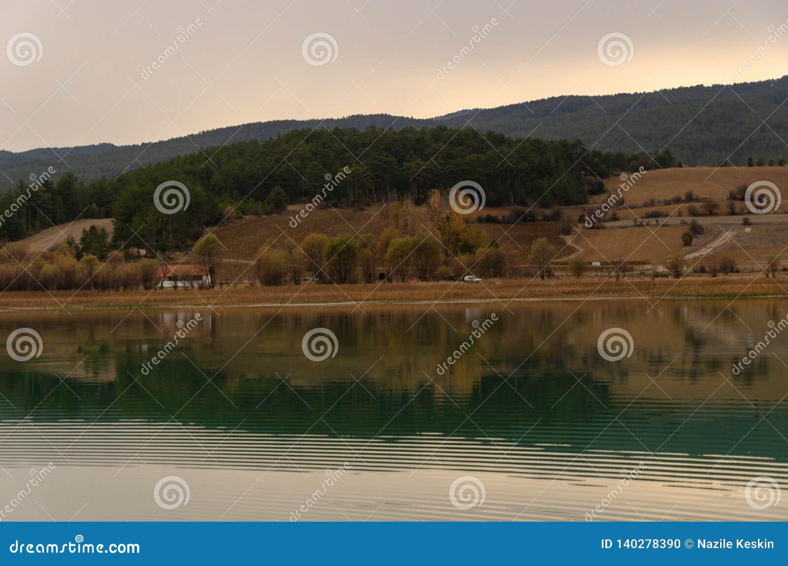 Kleines weißes Haus mit einer schönen Reflexion auf dem See vor ihm