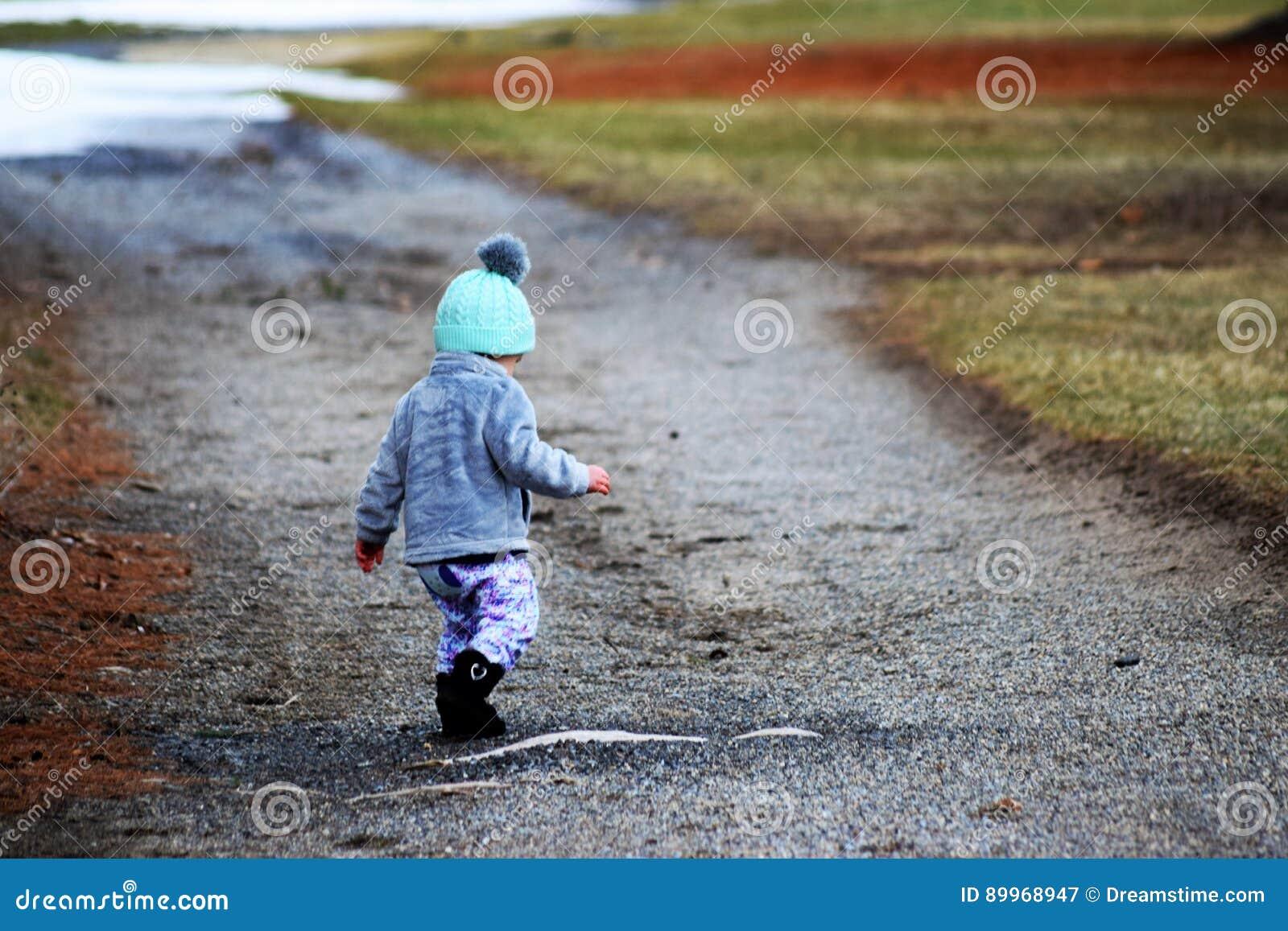 Kleinkind-Mädchen auf dem woodsy Weg, der unten schaut