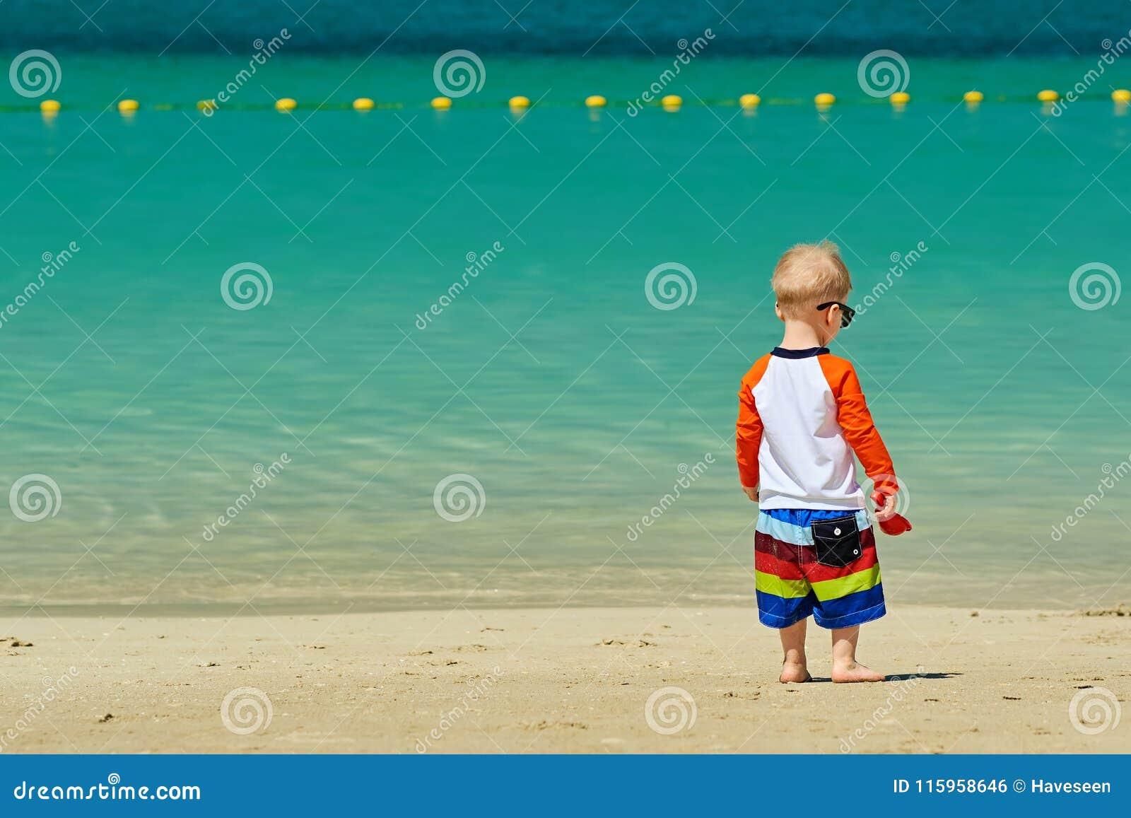 Kleinkindjunge mit zwei Jährigen, der auf Strand geht