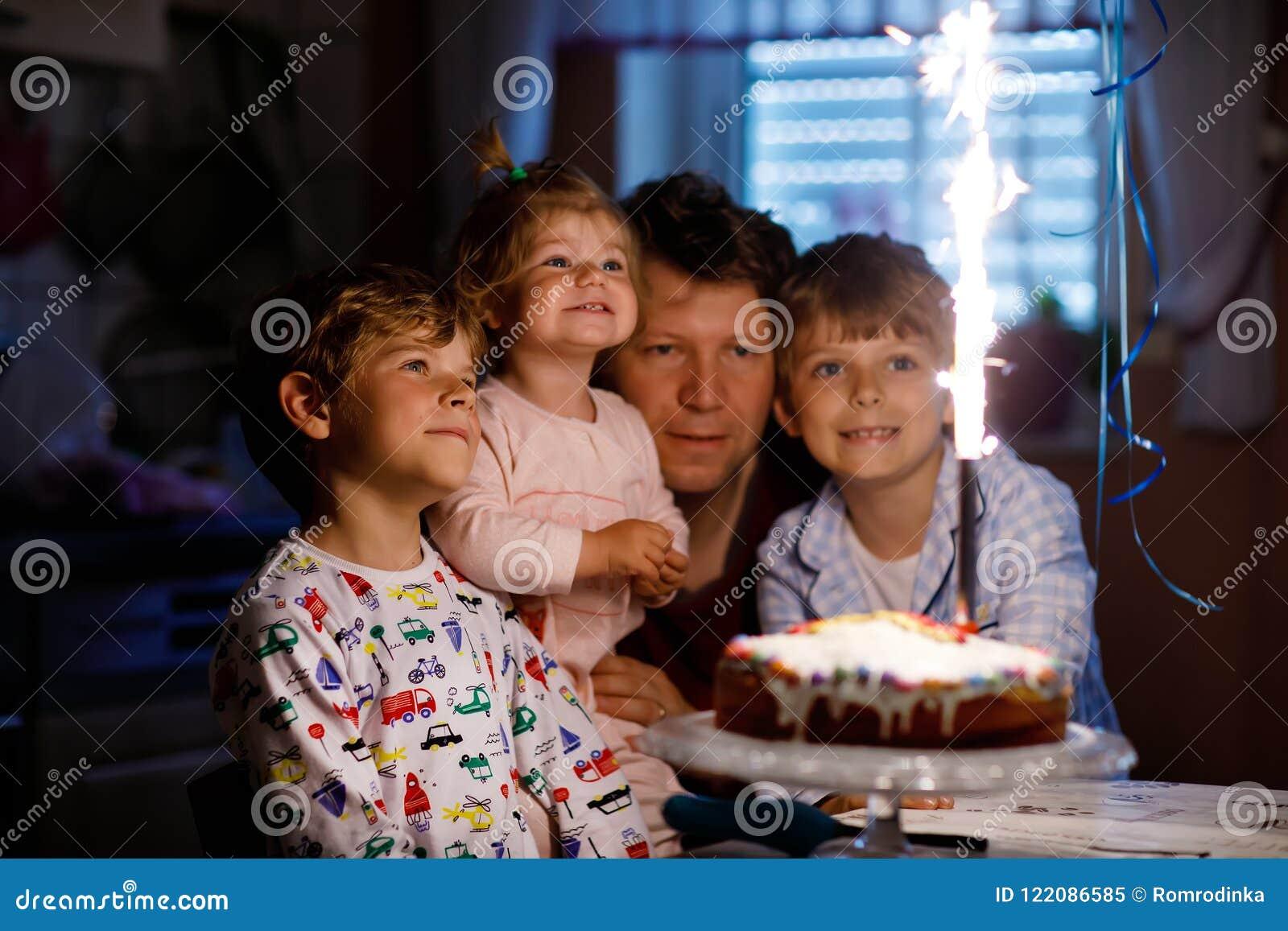 Kleinkindjunge und -familie, Vater, Bruder und kleines Schwesterchen, die Geburtstag feiern