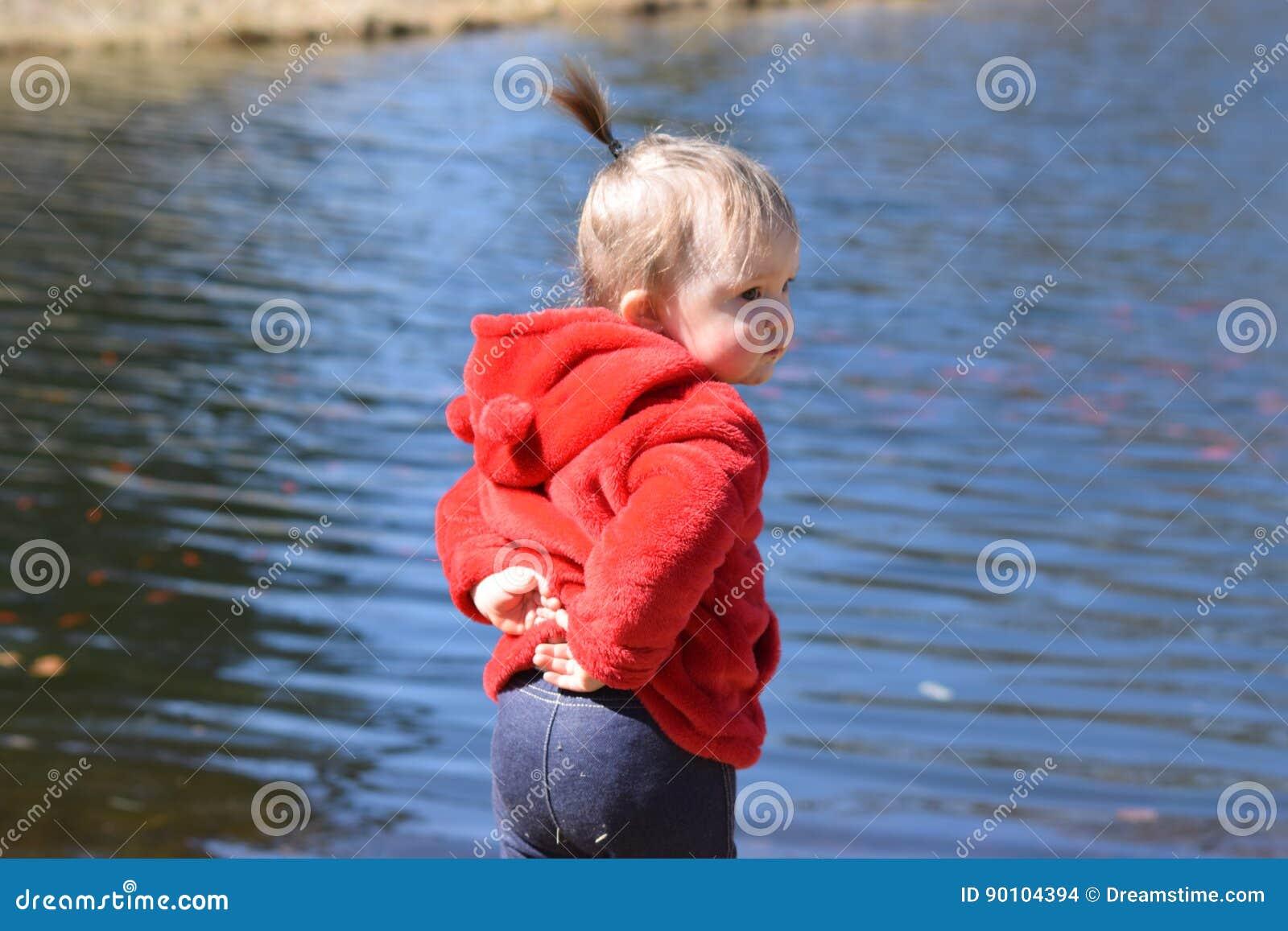 Kleinkindmädchen, das vor Teich steht