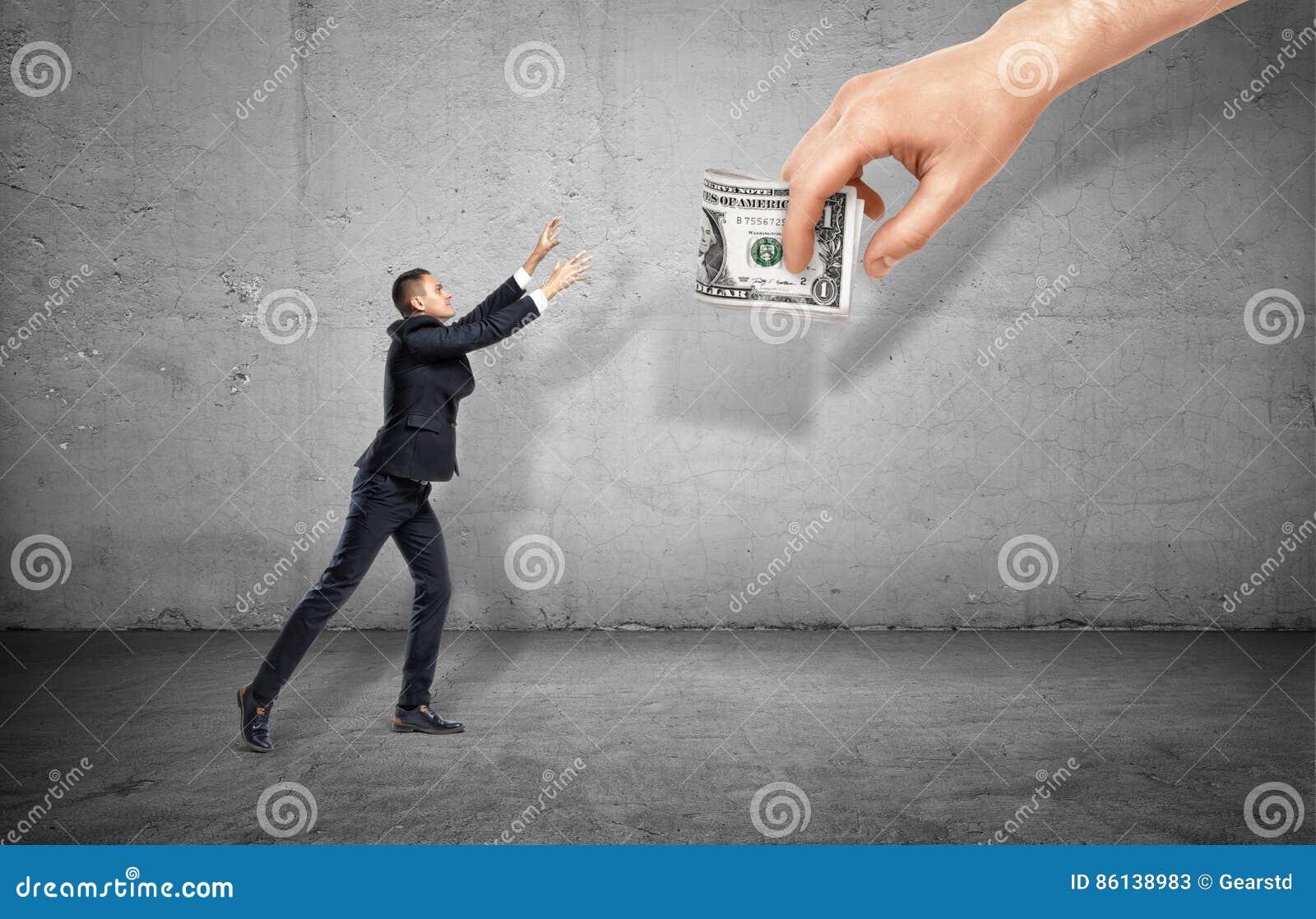 Kleinunternehmer auf dem konkreten Hintergrund, der heraus für eine riesige Hand hält Geld erreicht