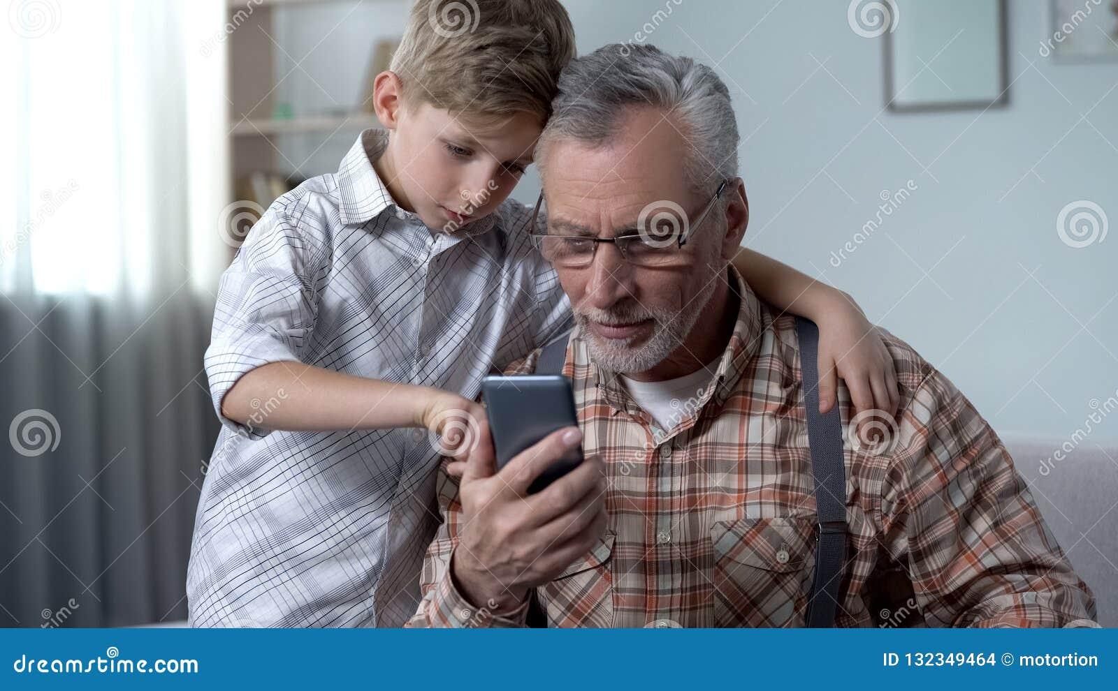 Kleinzoon die opa verklaren hoe te om smartphone, gemakkelijke toepassing voor bejaarden te gebruiken
