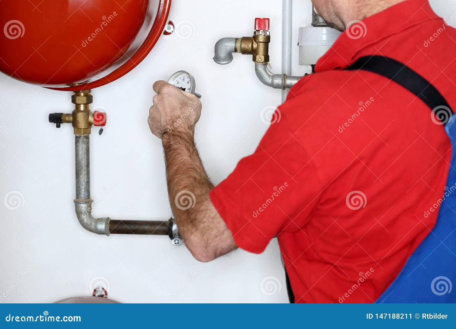 Klempner arbeitet in einem Heizungsraum