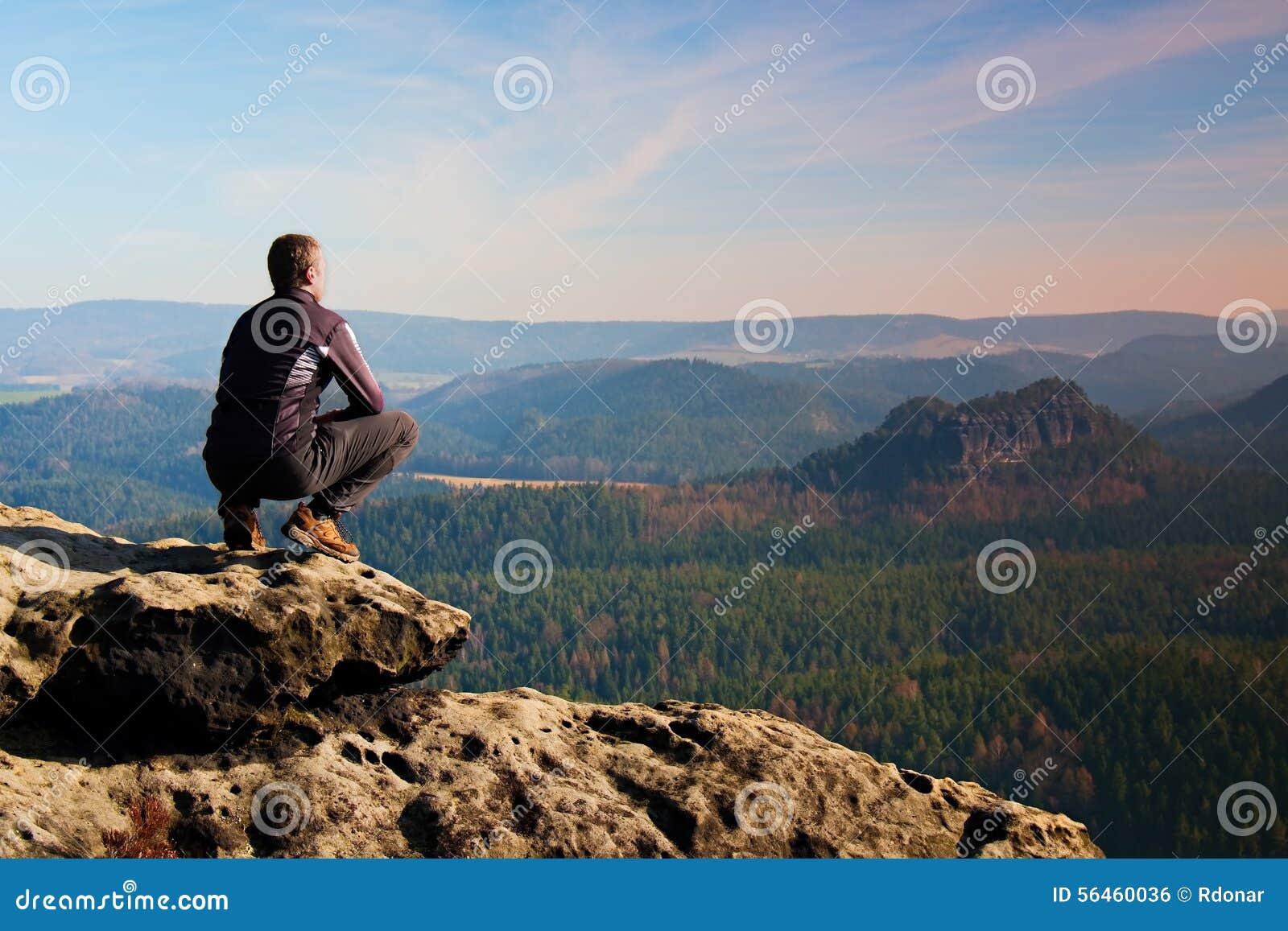 Kletternder erwachsener Mann an der Spitze des Felsens mit schöner Vogelperspektive des tiefen nebelhaften Tales brüllen