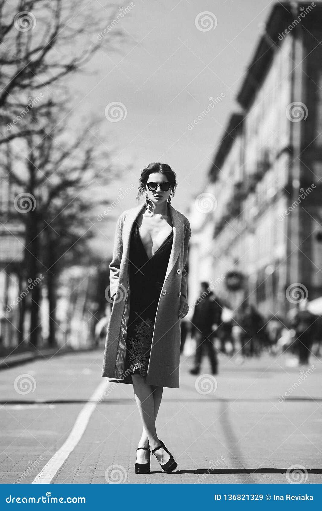 Kleurloze foto - mooi en sexy donkerbruin modelmeisje in de zwarte modieuze kleding, in een in laag en in modieus