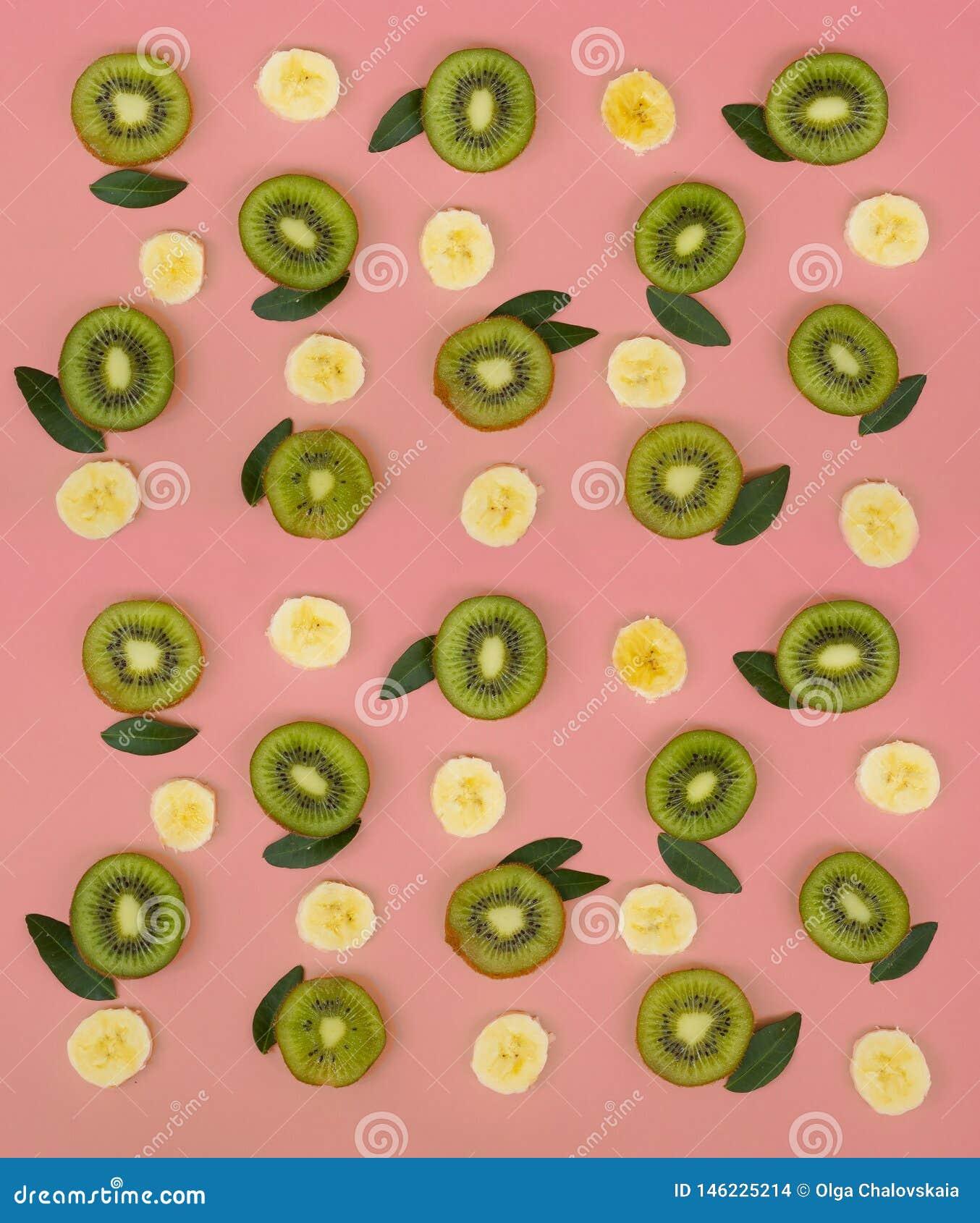 Kleurrijk fruitpatroon van verse kiwi en banaanplakken op roze achtergrond