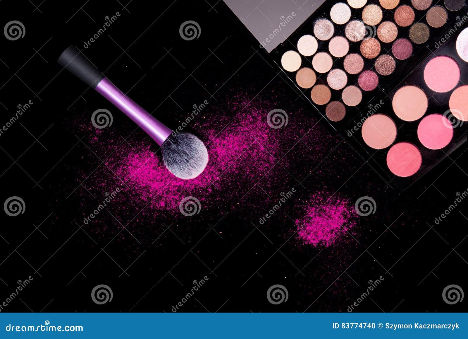 Kleurrijk make-uppalet en roze grote borstel om poeder op zuivere zwarte achtergrond toe te passen Professioneel make-upmateriaal