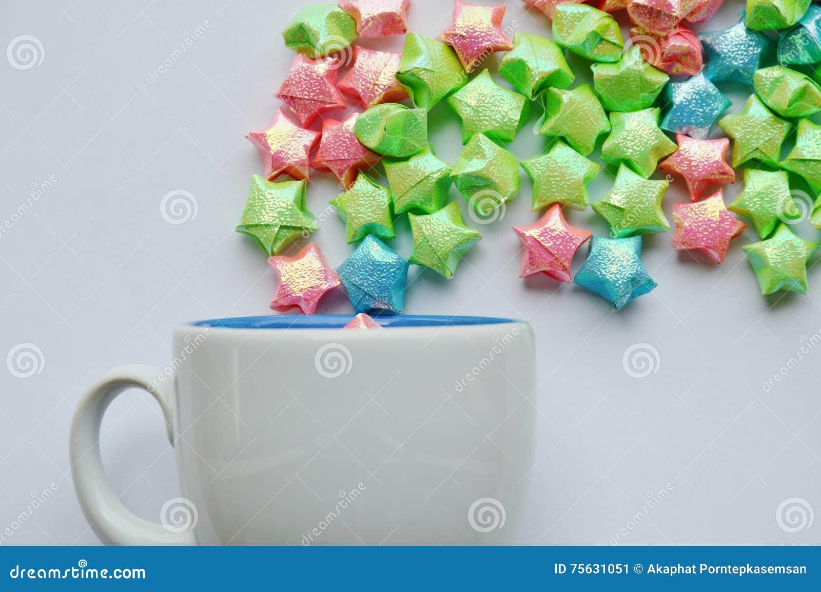 Kleurrijk sterdocument die van koffiekop drijven op witte achtergrond