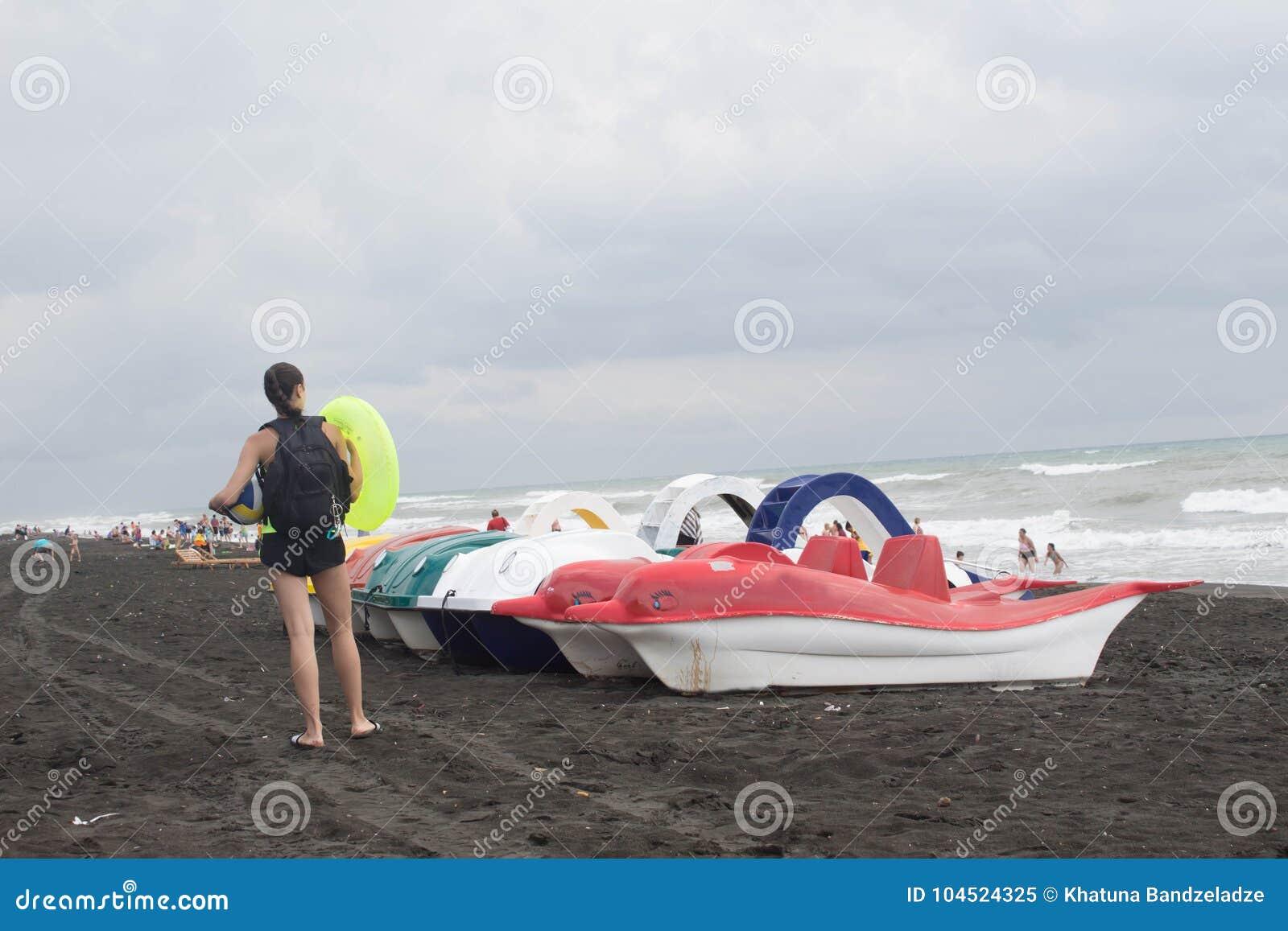 Kleurrijk van pedalo die op het strand, bewolking, wolken, golven wordt geparkeerd Meisje op het strand
