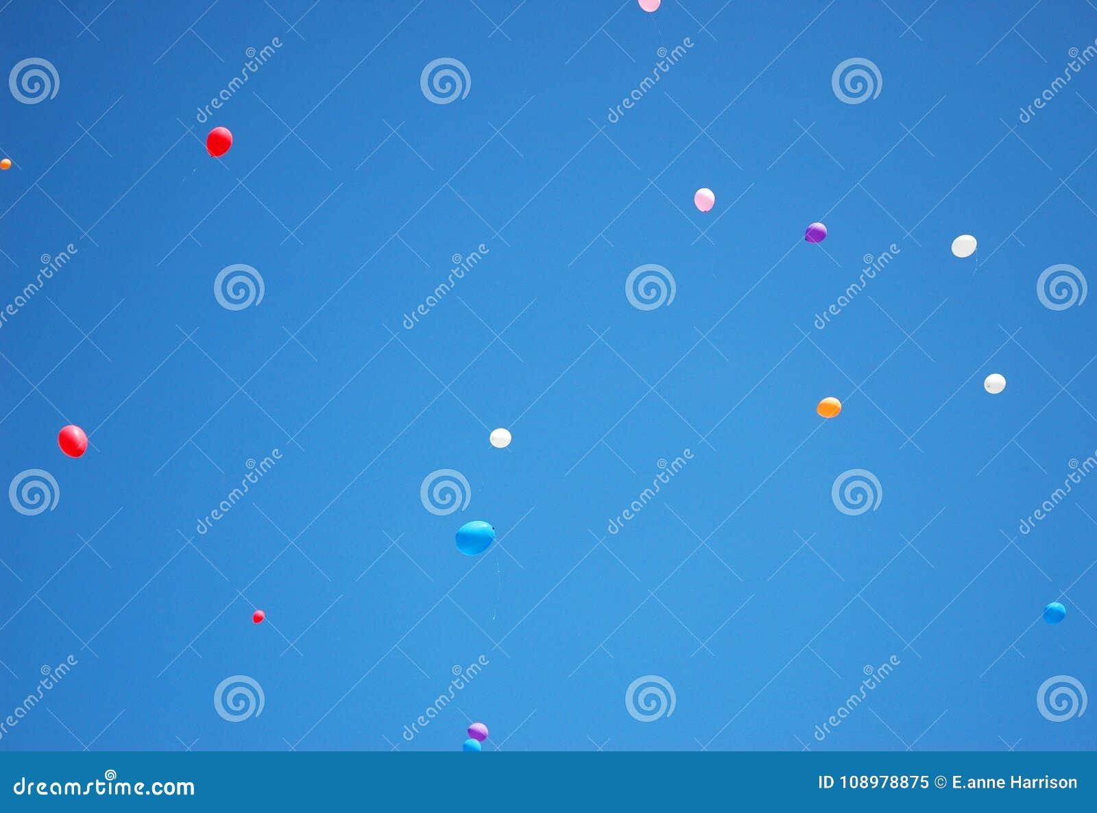 Kleurrijke ballons die weg in een blauwe hemel ontsnappen