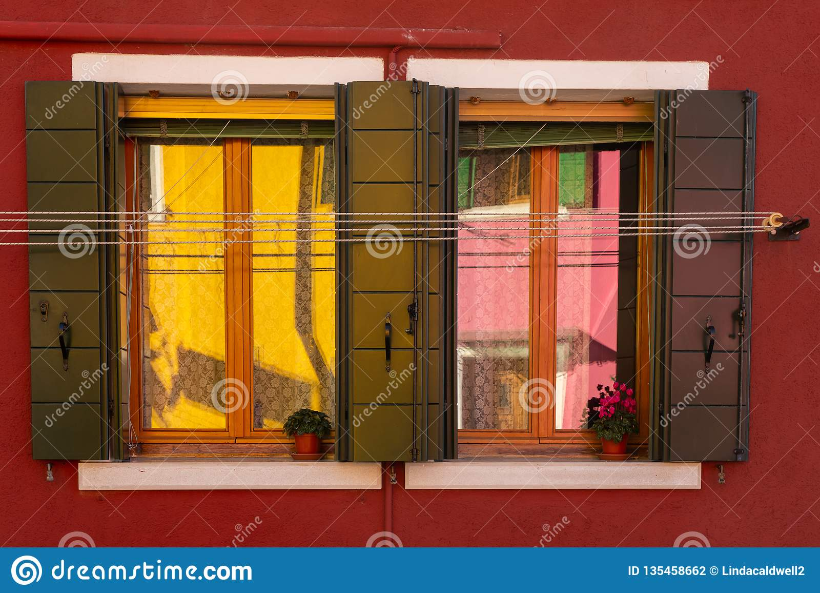 Kleurrijke bezinningen in een venster op Burano