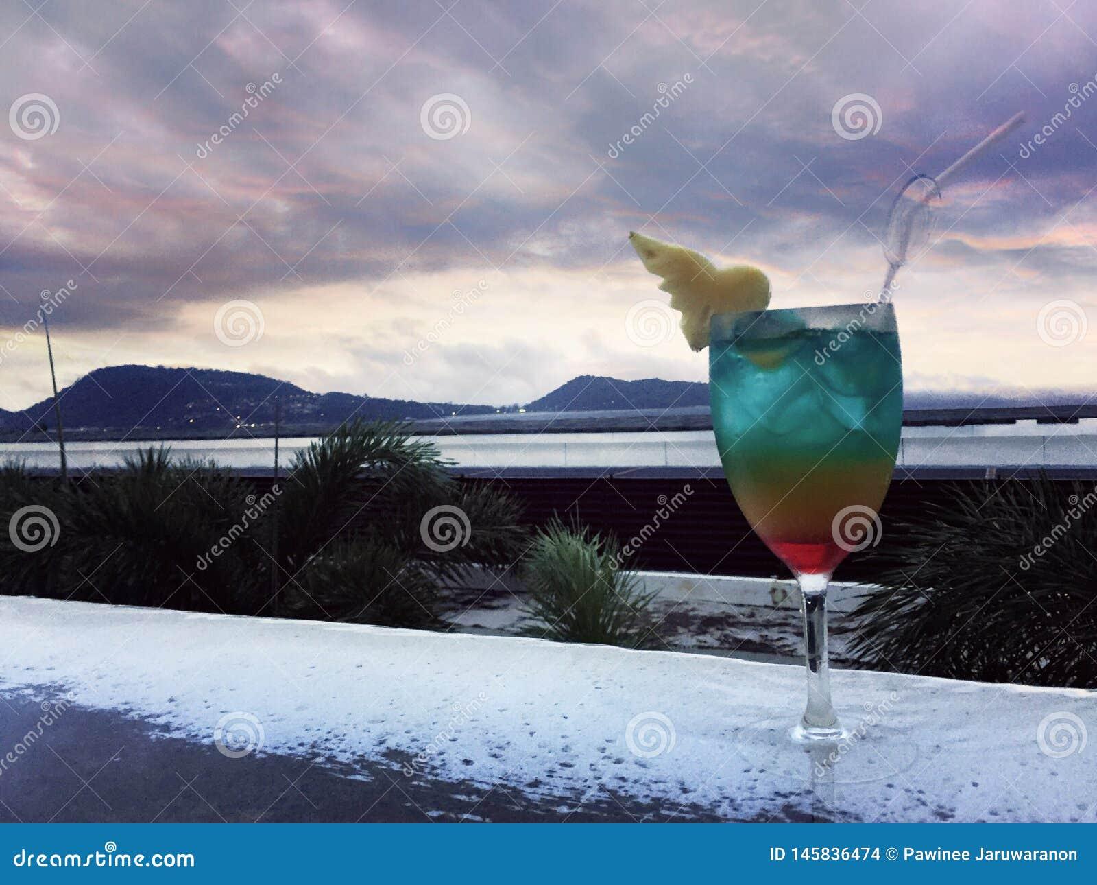 Kleurrijke cocktail bij de rand van zwembad voor overzeese mening