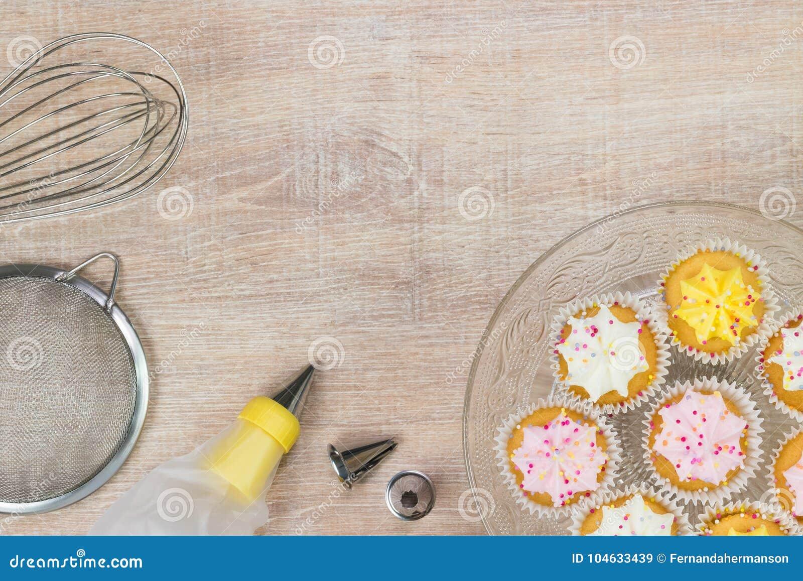 Download Kleurrijke Cupcakes En Bakselhulpmiddelen Op Een Houten Lijstachtergrond Stock Afbeelding - Afbeelding bestaande uit pastei, suikerglazuur: 104633439