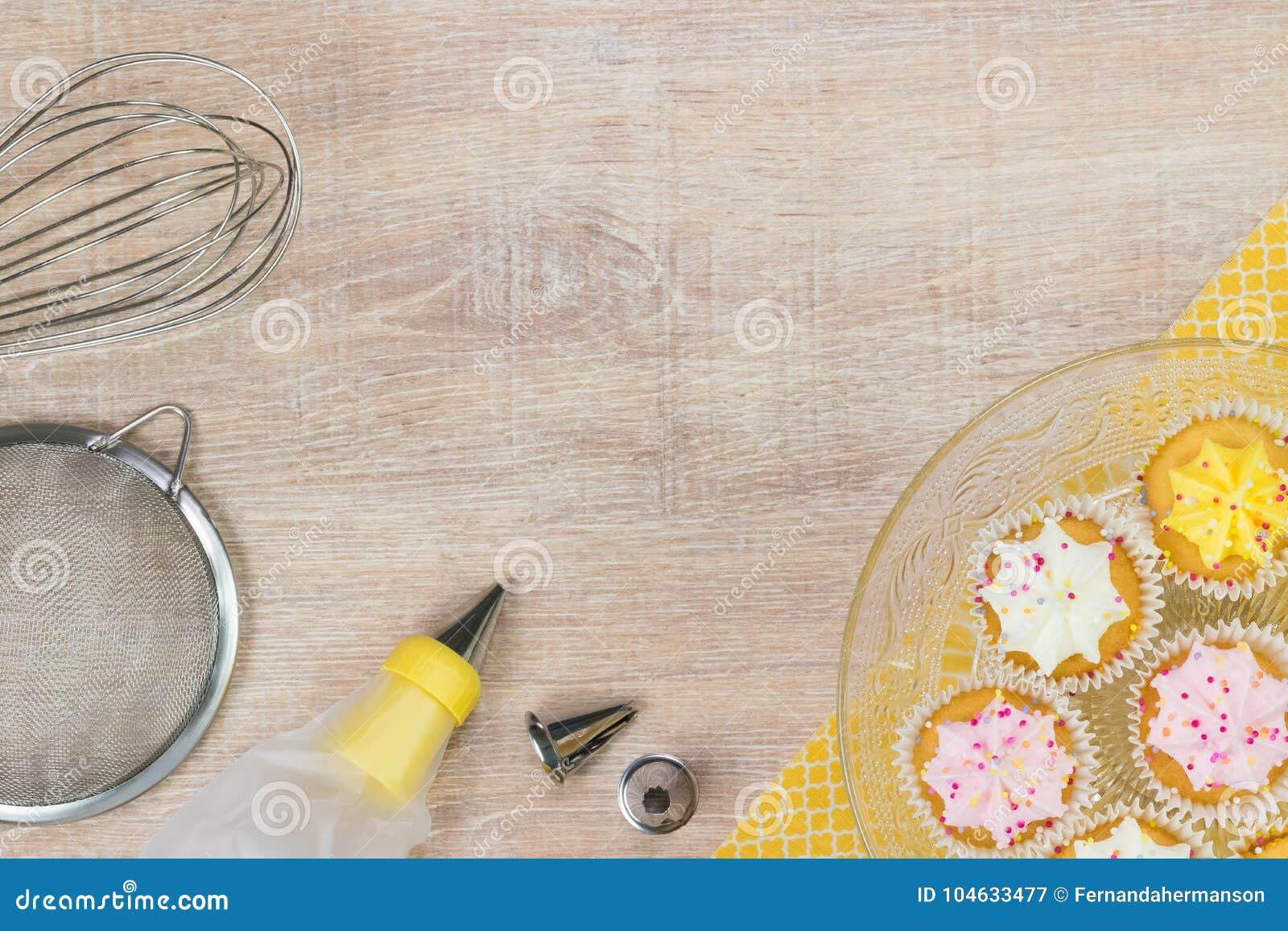 Download Kleurrijke Cupcakes En Bakselhulpmiddelen Op Een Houten Lijstachtergrond Stock Afbeelding - Afbeelding bestaande uit exemplaar, pijp: 104633477