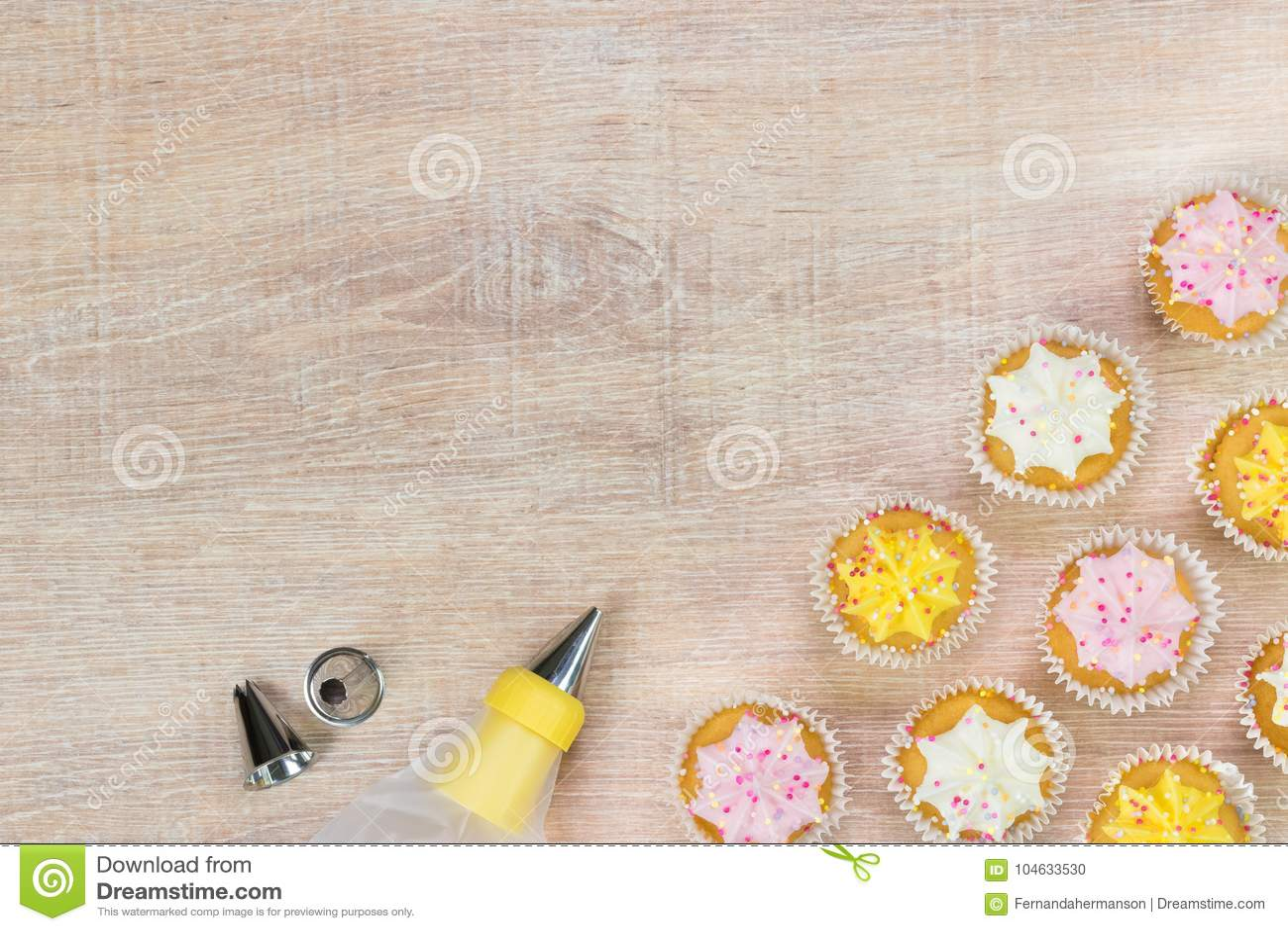 Download Kleurrijke Cupcakes En Bakselhulpmiddelen Op Een Houten Lijstachtergrond Stock Foto - Afbeelding bestaande uit vakantie, feestelijk: 104633530