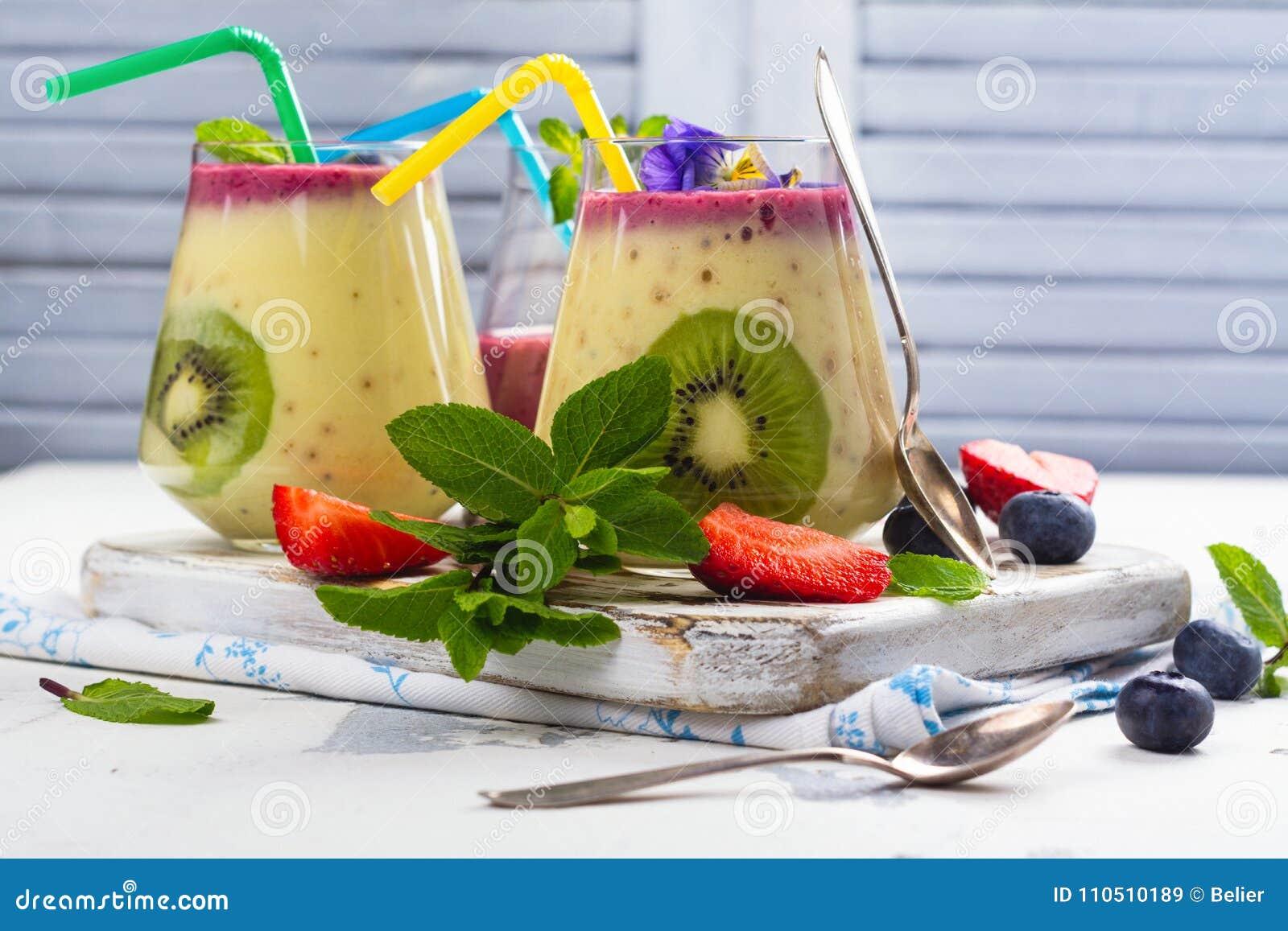 Kleurrijke detox gelaagd smoothie met natuurlijke eetbare bloemen, bessen en munt