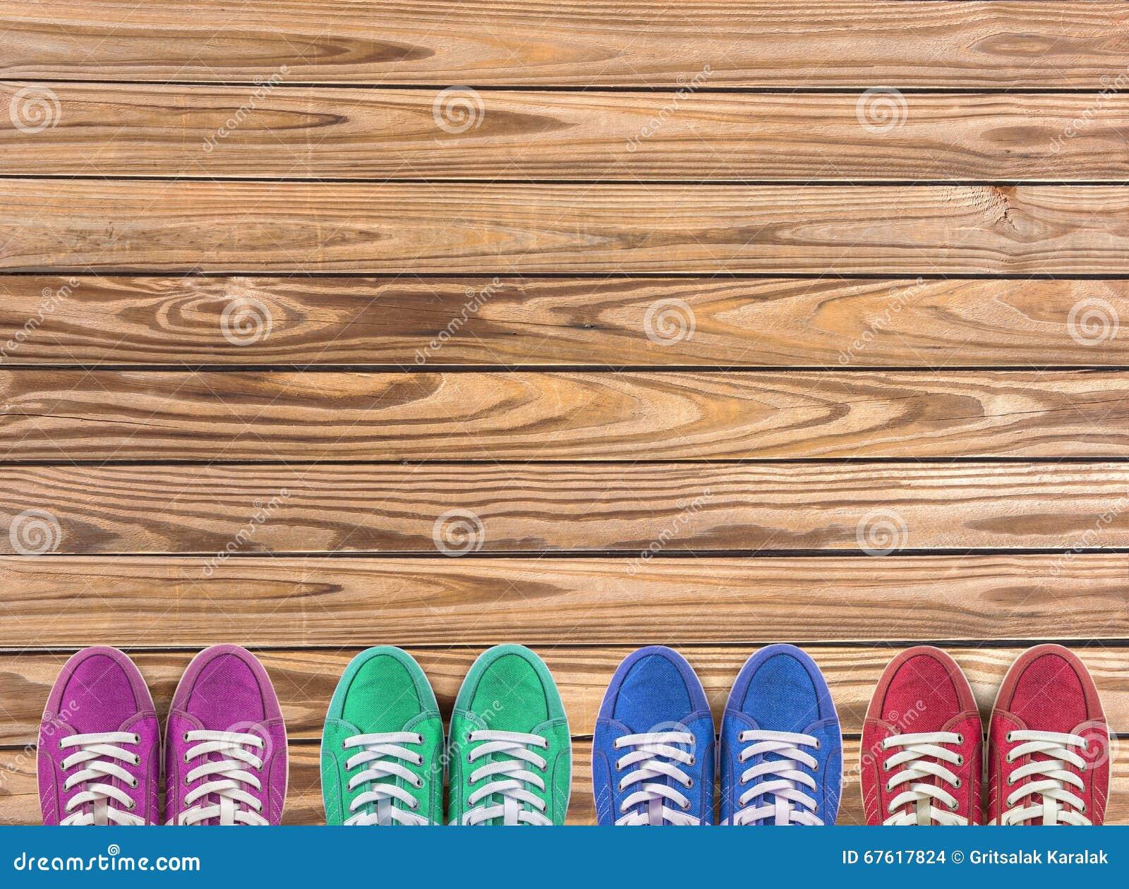 Kleurrijke die schoenen op houten achtergrond met exemplaarruimte worden geplaatst Hoogste mening