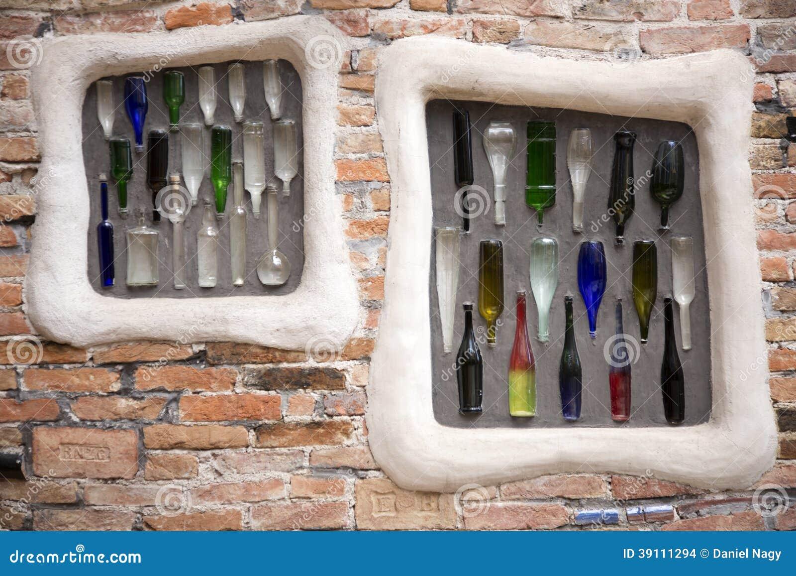 Kleurrijke flessen ingebed in bakstenen muur