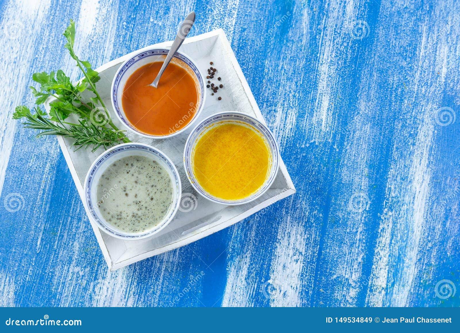 Kleurrijke groene, gele en rode kruidige sausen in kommen in een witte die plaat op blauwe houten geschilderde plank wordt ge?sol