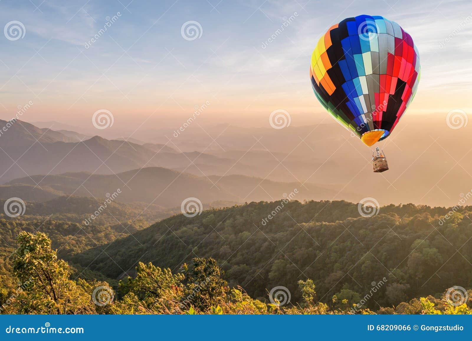 Kleurrijke hete luchtballon over hoge berg bij zonsondergang