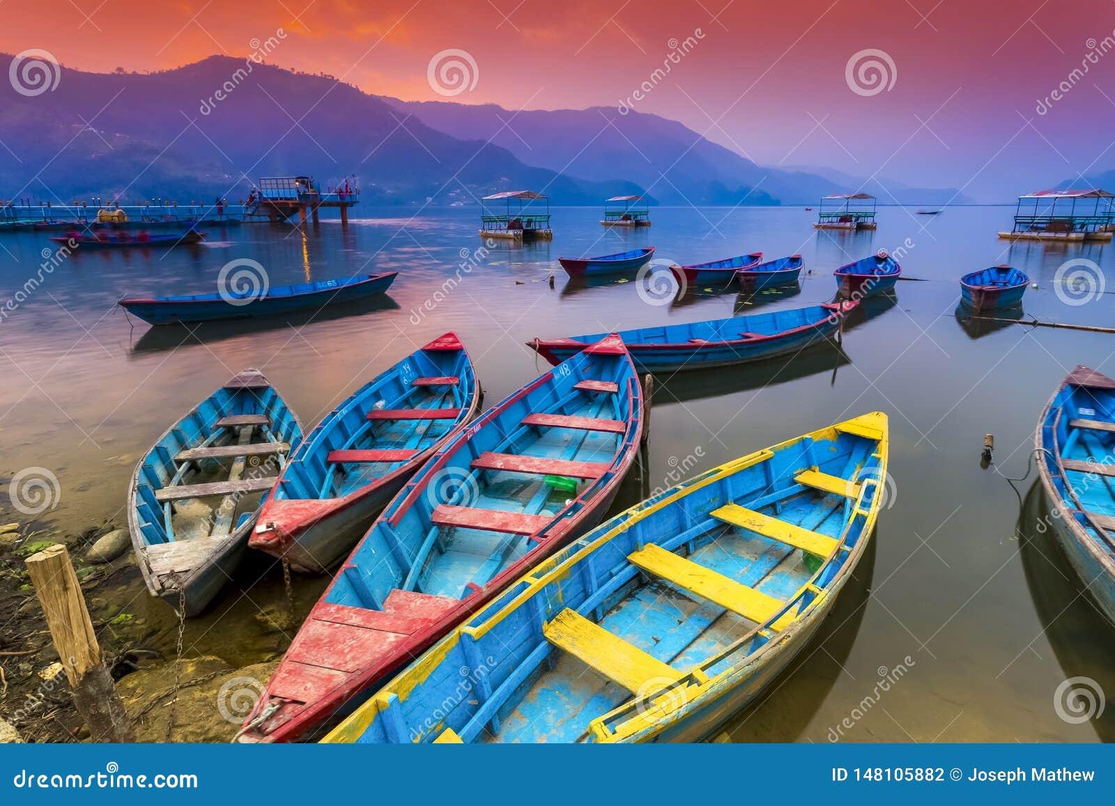 Kleurrijke Houten Boten die in Phewa-meer en verbazende Zonsondergang op Achtergrond parkeren