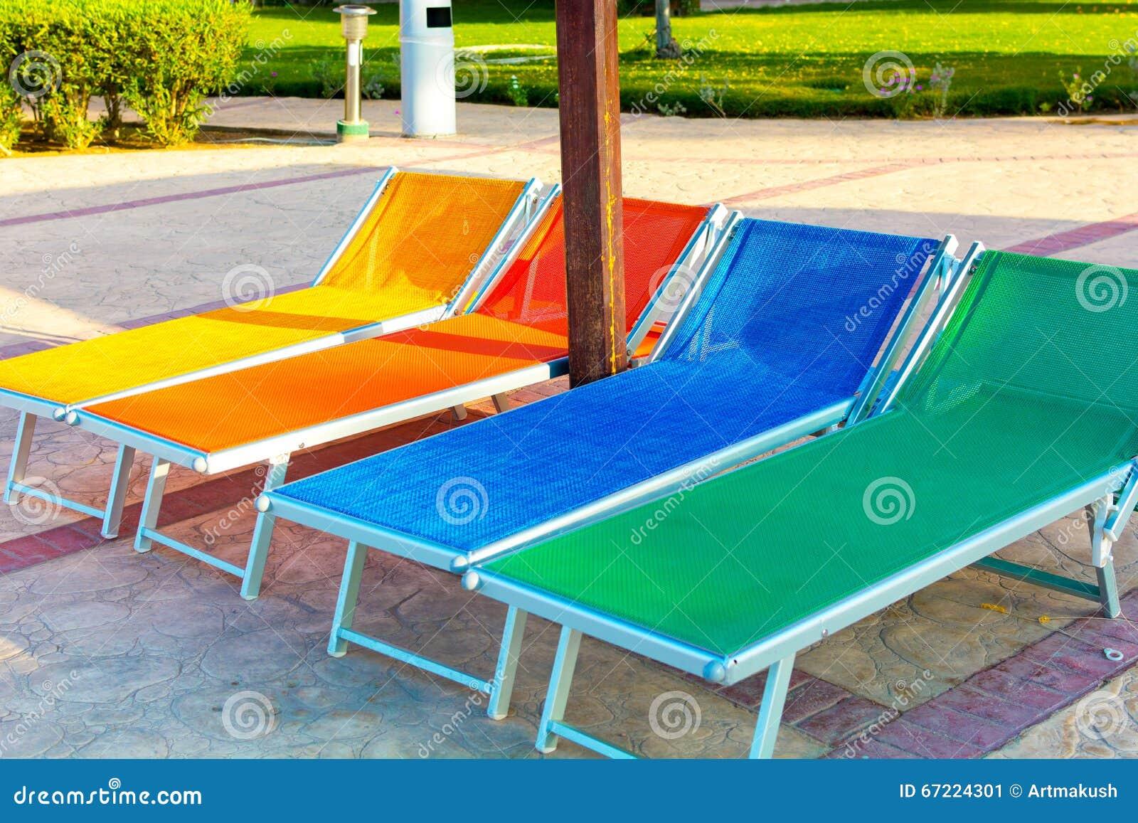 Kleurrijke houten chaise zitkamers in zwembad stock foto afbeelding 67224301 - Houten strand zwembad ...