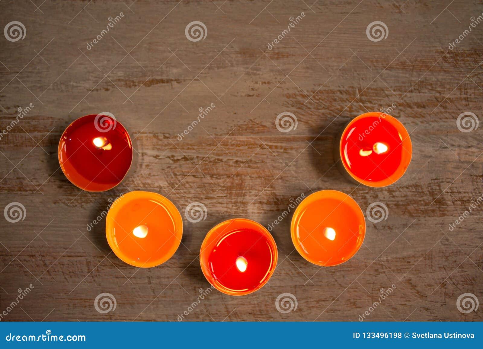 Kleurrijke kaarsen op de houten raad