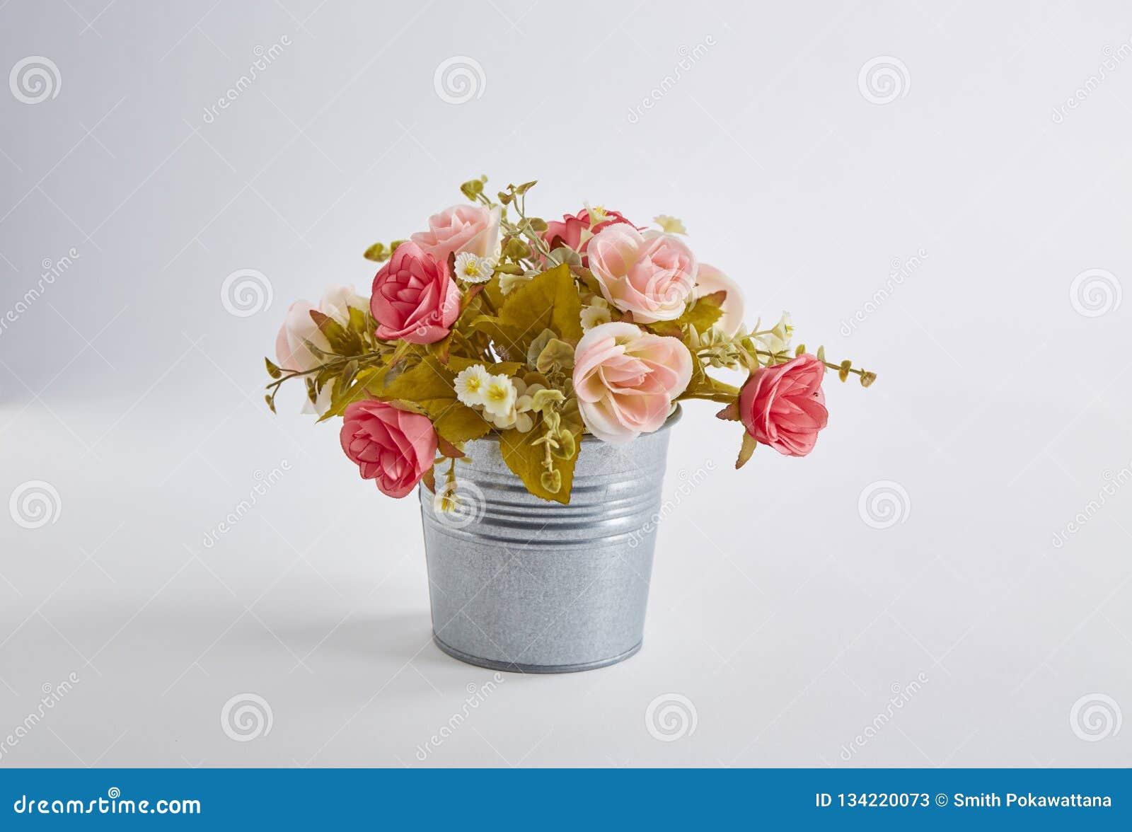 Kleurrijke kunstmatig nam bloemen in pot op witte achtergrond toe