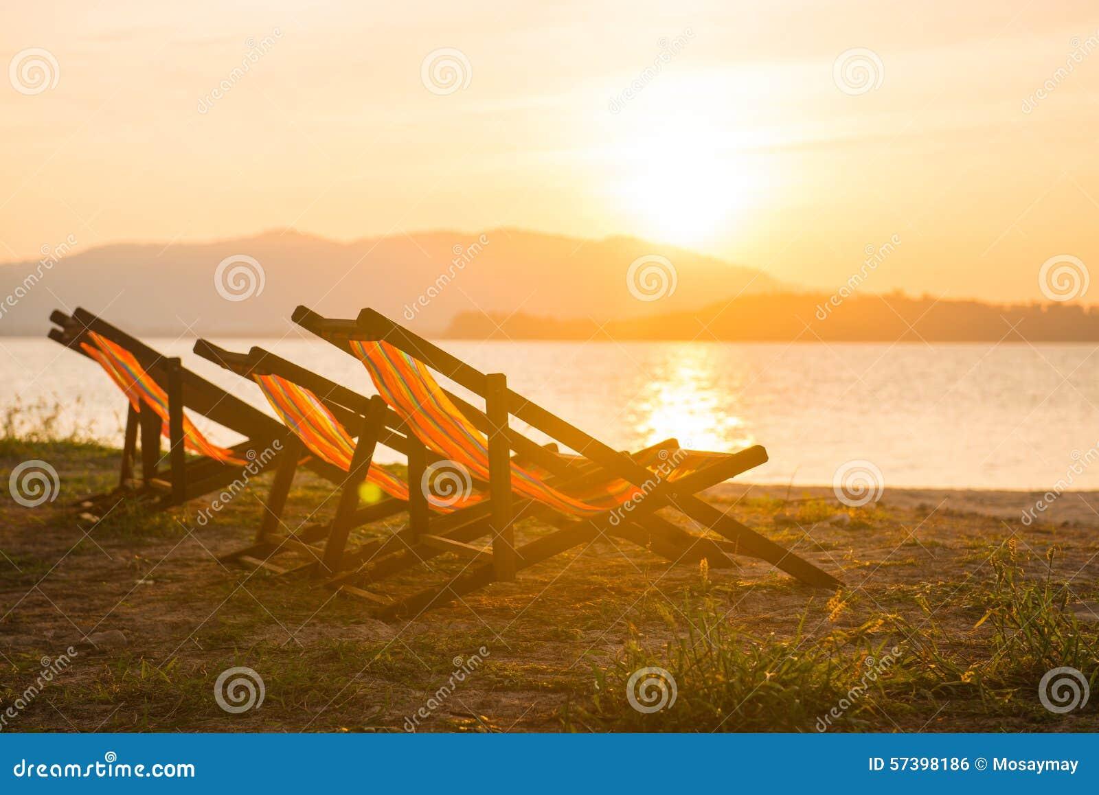 Kleurrijke ligstoel op het strand in zonsondergangtijd