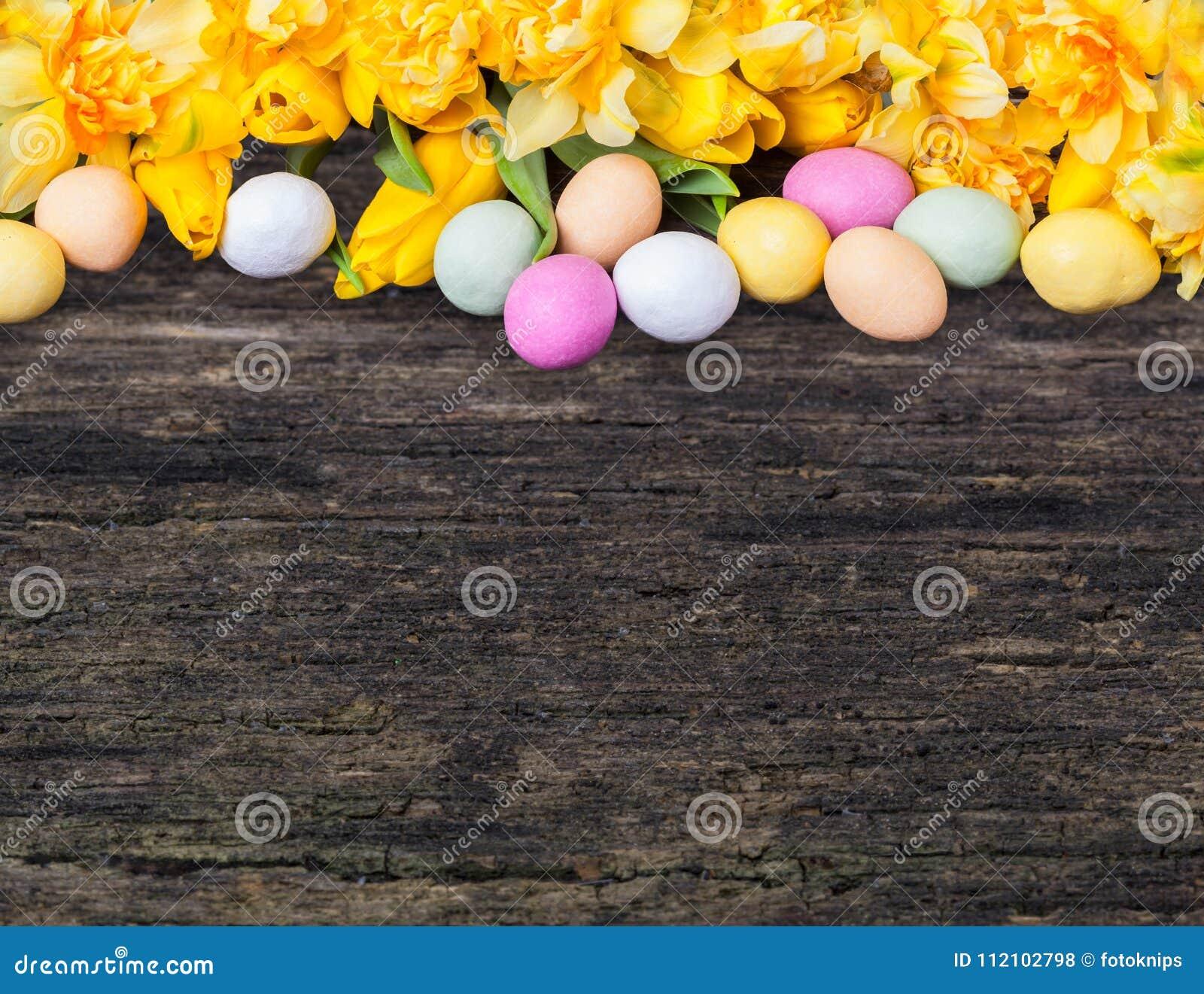 Kleurrijke paaseieren en gele narcissen en tulpen op hout