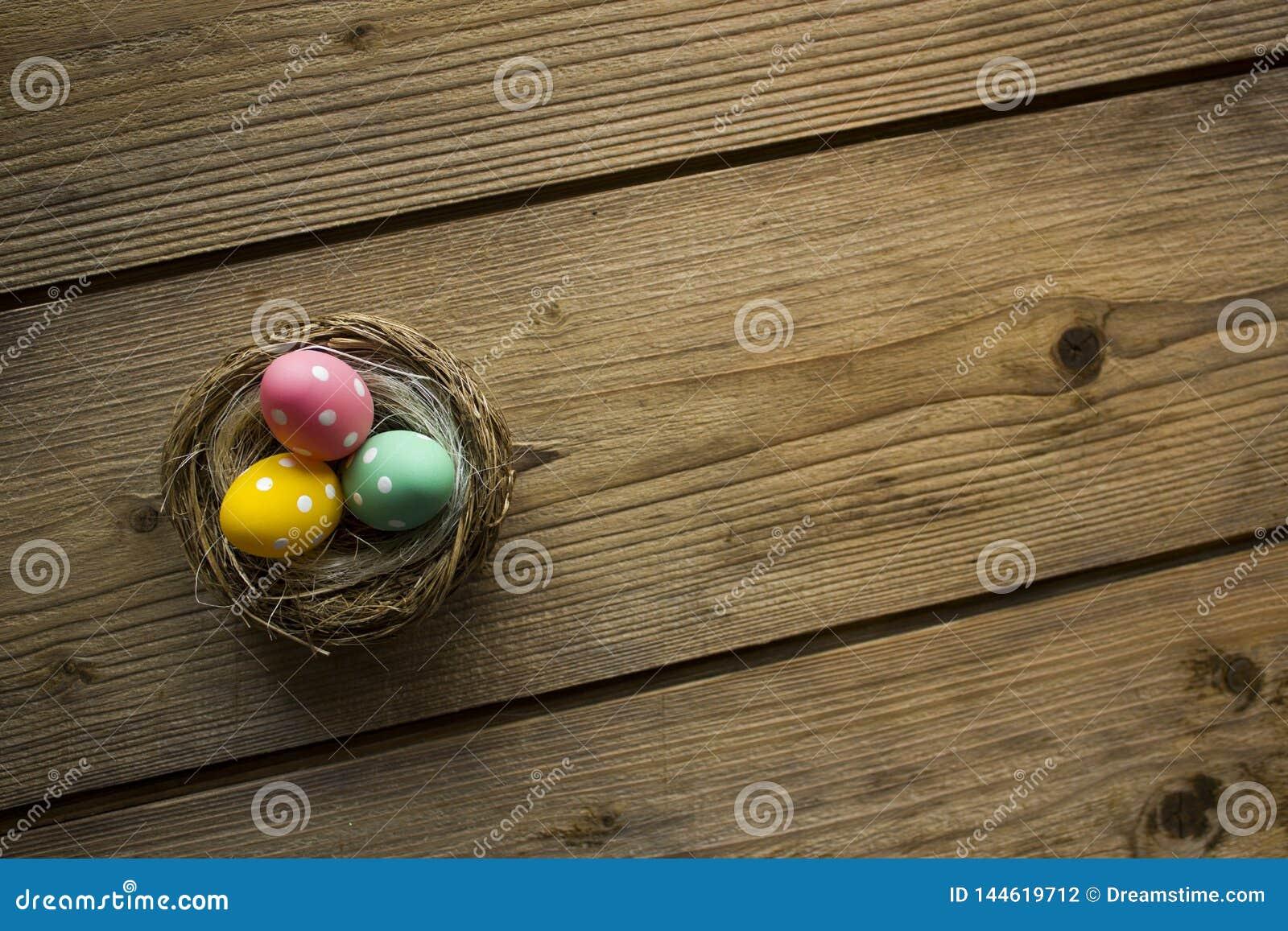 Kleurrijke paaseieren in nest op houten lijst