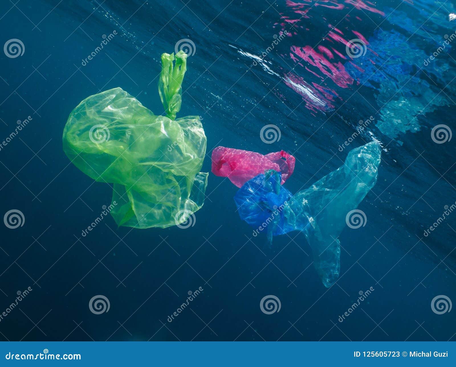 Kleurrijke plastic zakken die in de oceaan drijven