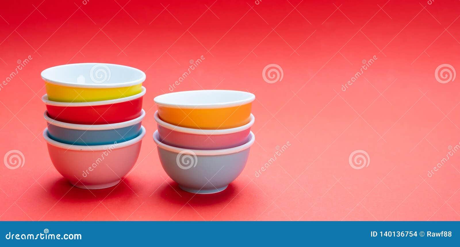 Kleurrijke schone ceramische die kommen op rode kleurenachtergrond worden gestapeld, exemplaarruimte