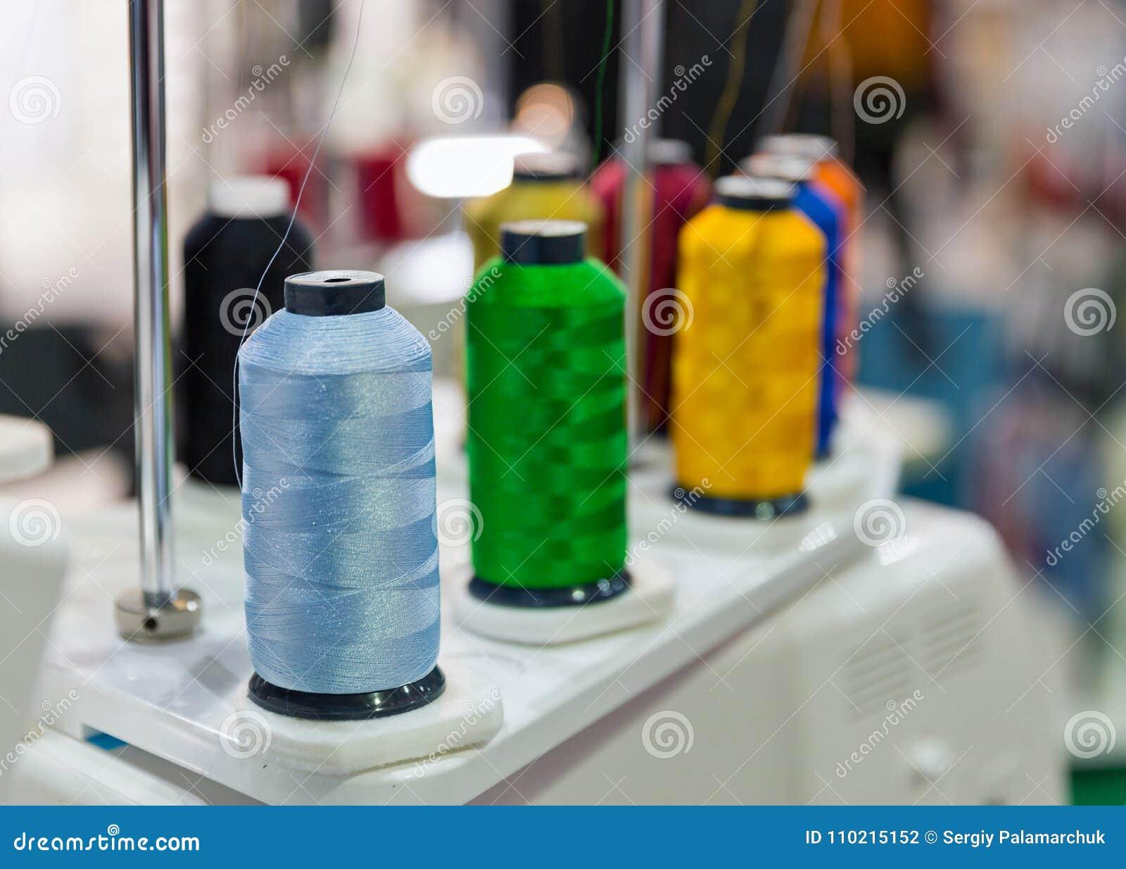 Kleurrijke spoelen van draden op professionele machine om borduurwerk toe te passen
