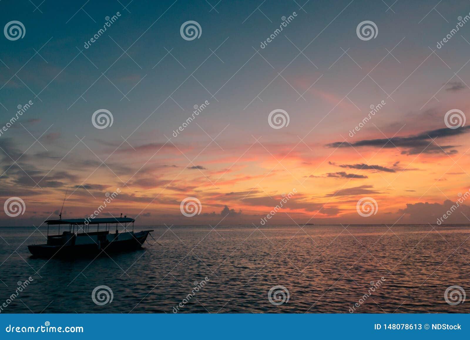 Kleurrijke zonsondergangbezinning over een bewolkte hemel en een overzees weinig boot op de oceaan