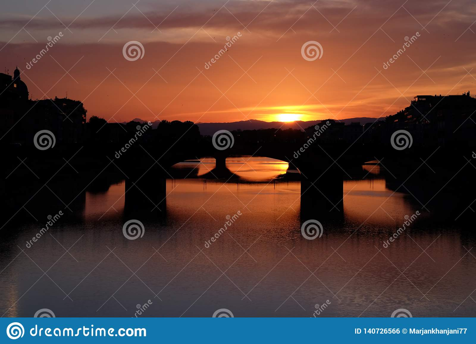 Kleurrijke zonsondergangmening van Arno-rivier in Florence, Italië