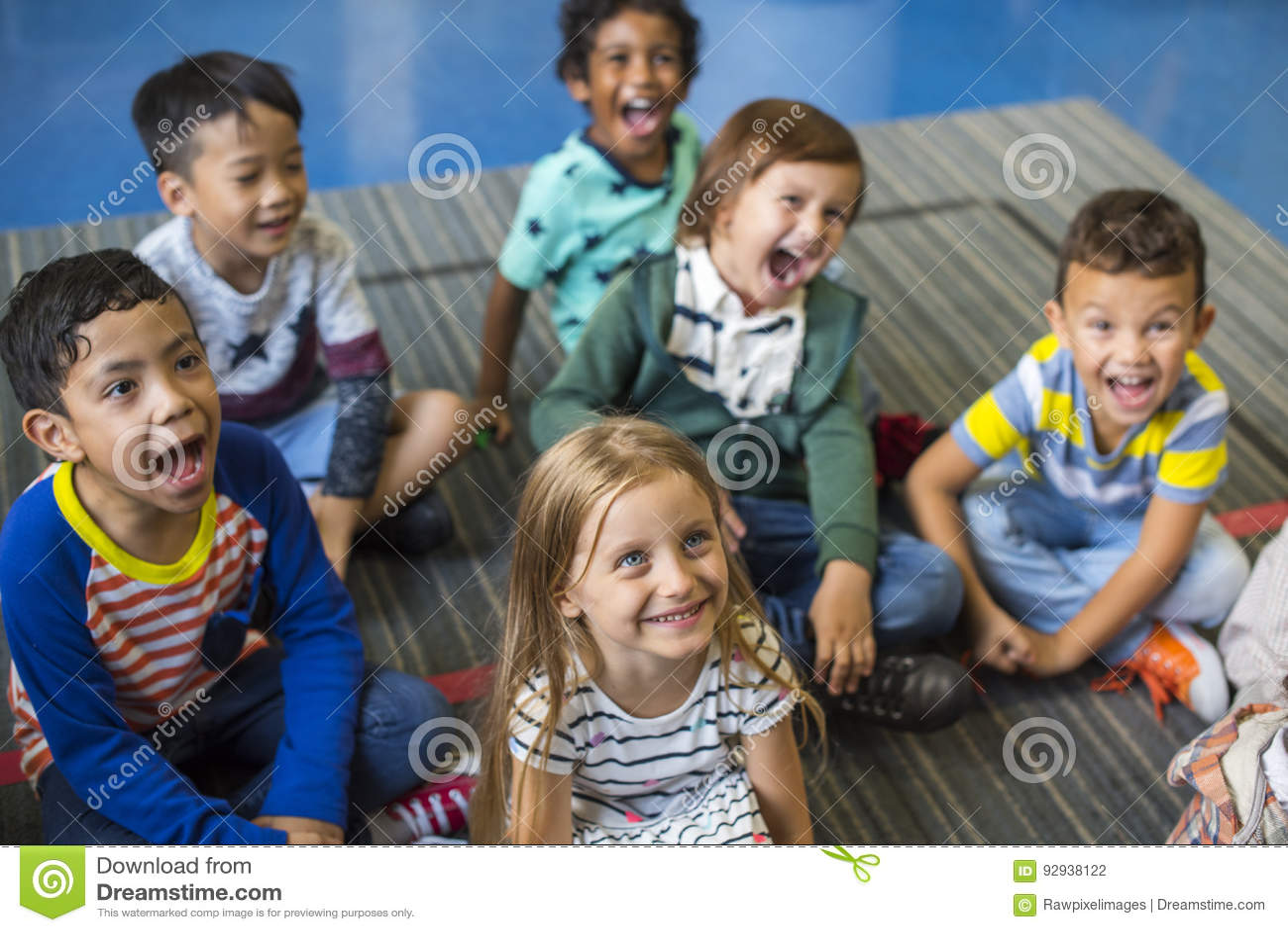 Kleuterschoolstudenten die op de vloer zitten
