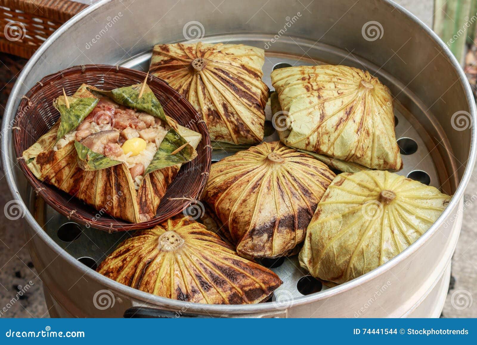 Klibbigt ris som slås in i lotusblommablad eller Zongzi, är traditionell kines som mat göras med klibbiga ris