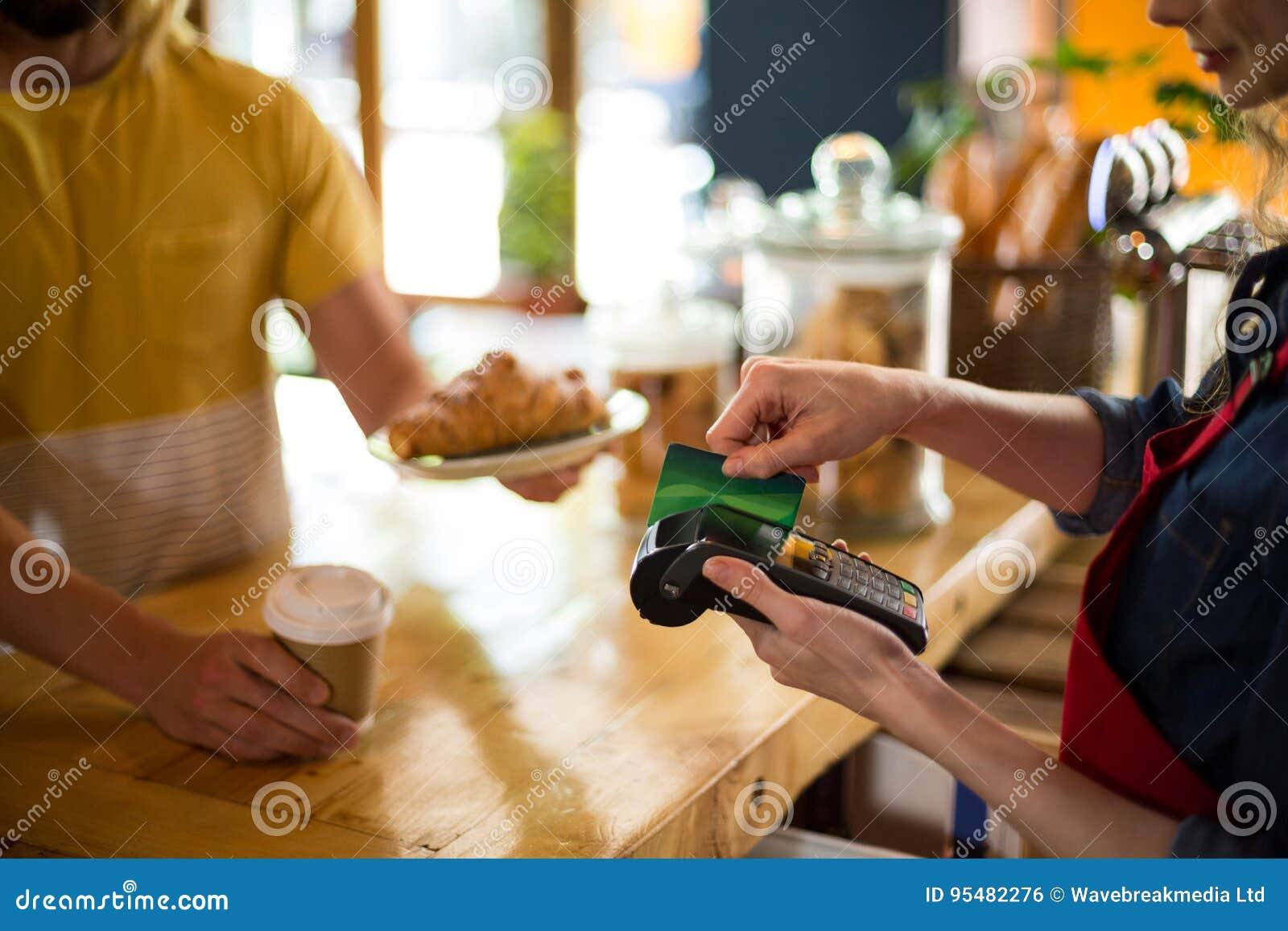 Klient robi zapłacie przez kredytowej karty przy kontuarem w café