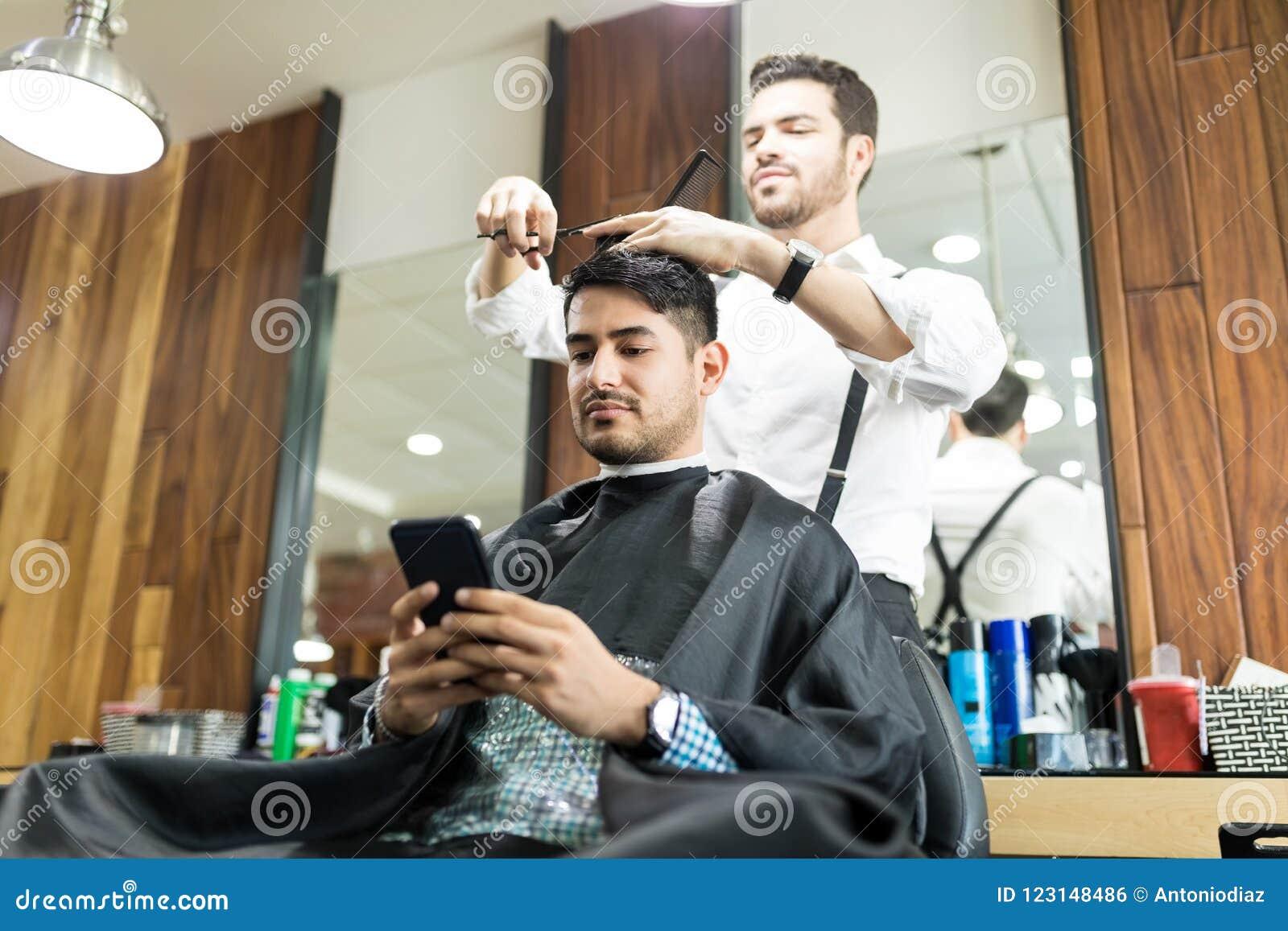 Klient Używa Smartphone Podczas gdy fryzjer Daje On ostrzyżeniu