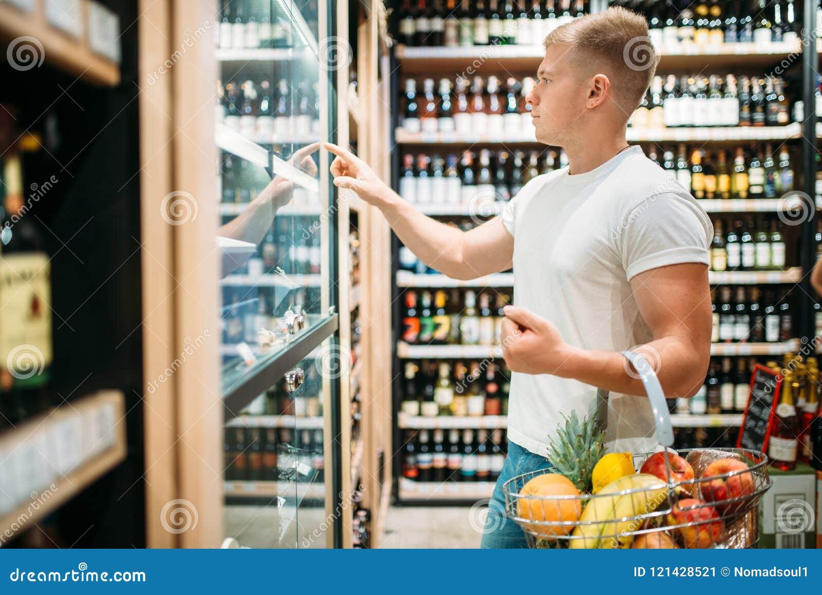 Klient wybiera piwo w supermarkecie z koszem