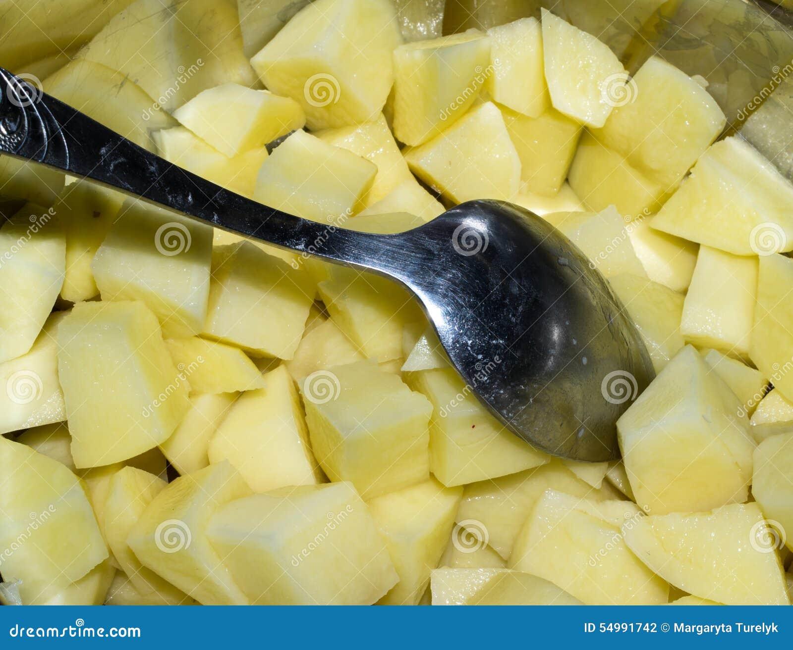 Klipp rå potatisar och skeden i en kastrull